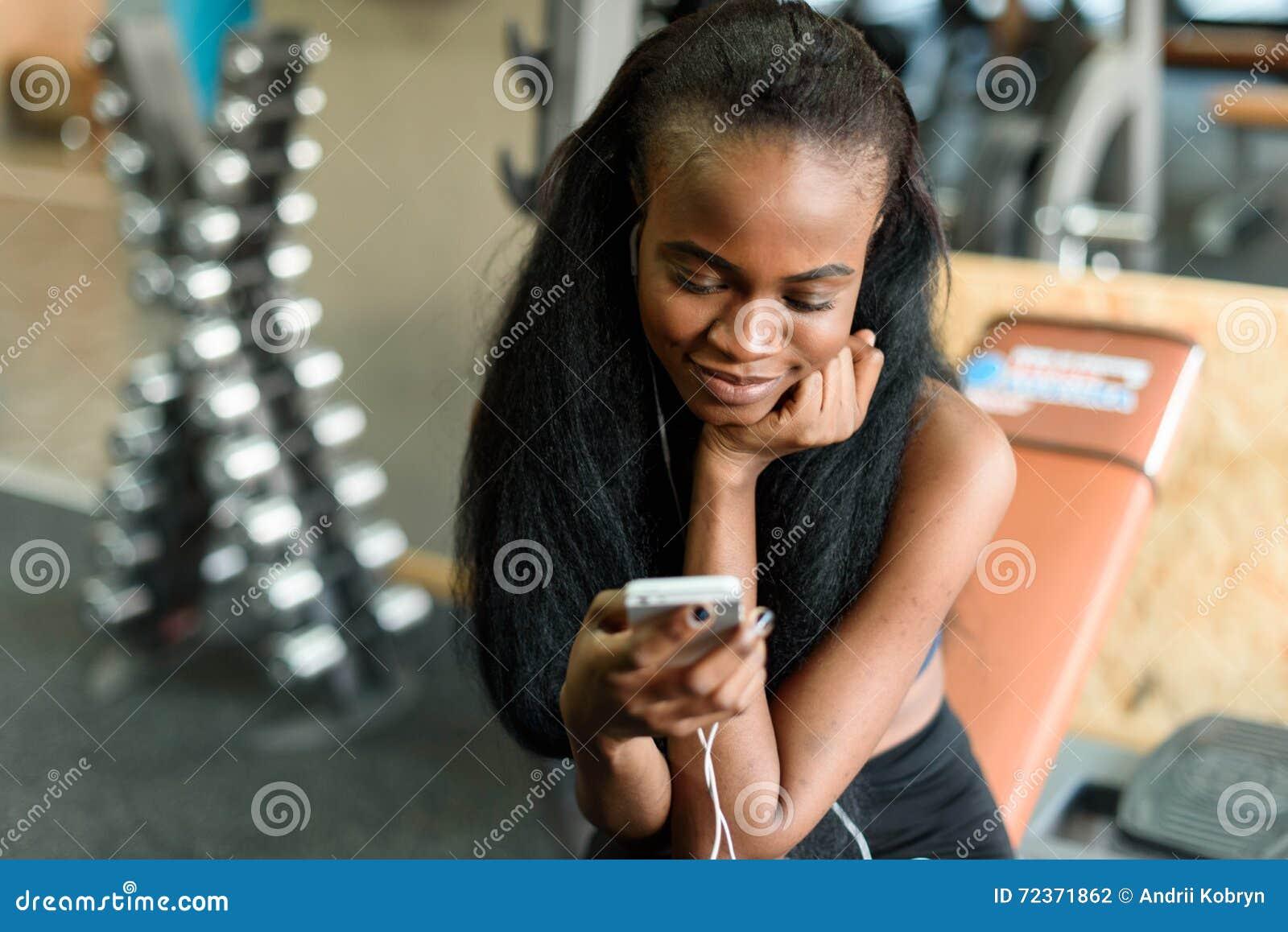 华美的黑人夫人画象有发短信在她的在健身房的智能手机的豪华长的头发的