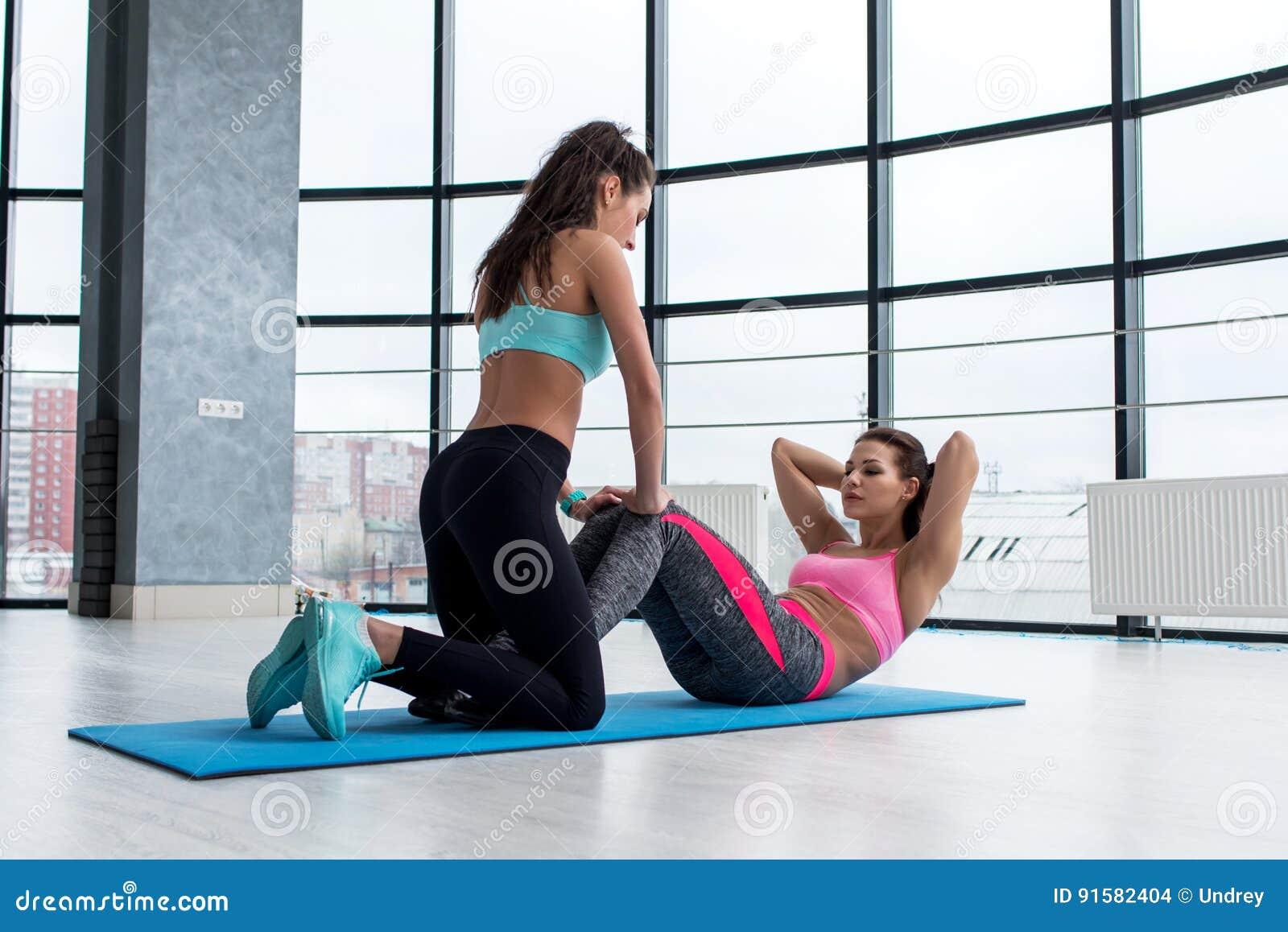 协助相当亭亭玉立的运动的女孩的专业女性个人教练员做说谎在健身房的地板上的胃肠咬嚼