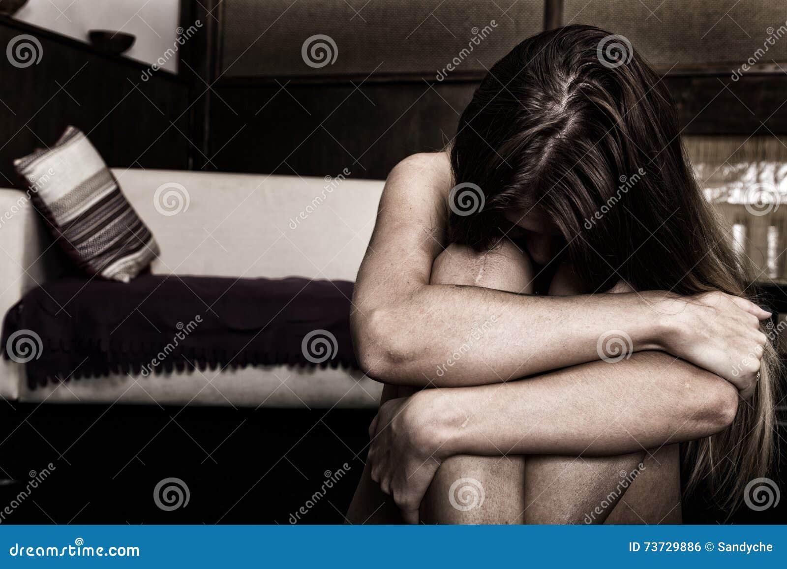 单独坐在一间空的屋子的哀伤的妇女在床旁边 查出的背景国内现有量题头保护自己给新暴力的白人妇女