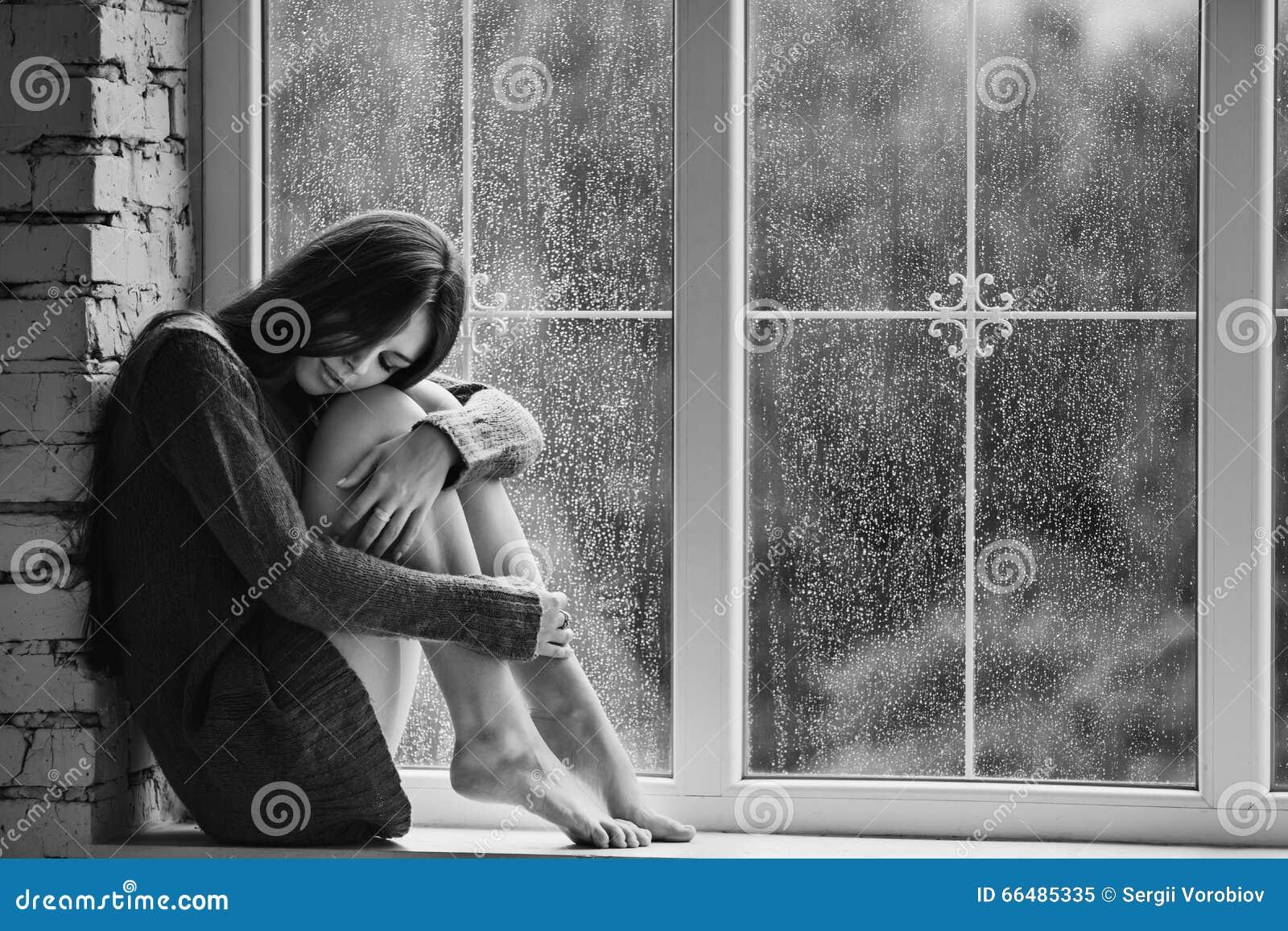 单独坐接近与雨的窗口的美丽的少妇滴下 性感和哀伤的女孩 寂寞的概念 投反对票
