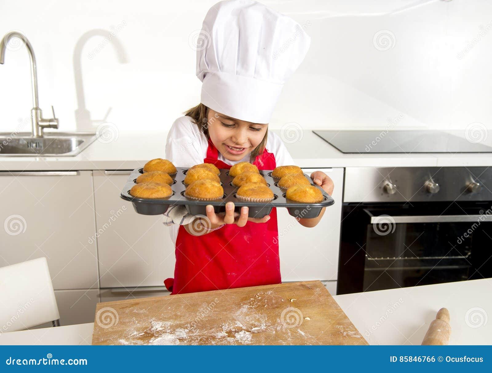 单独小和逗人喜爱的女孩提出和显示有松饼微笑的厨师帽子和围裙的盘子愉快