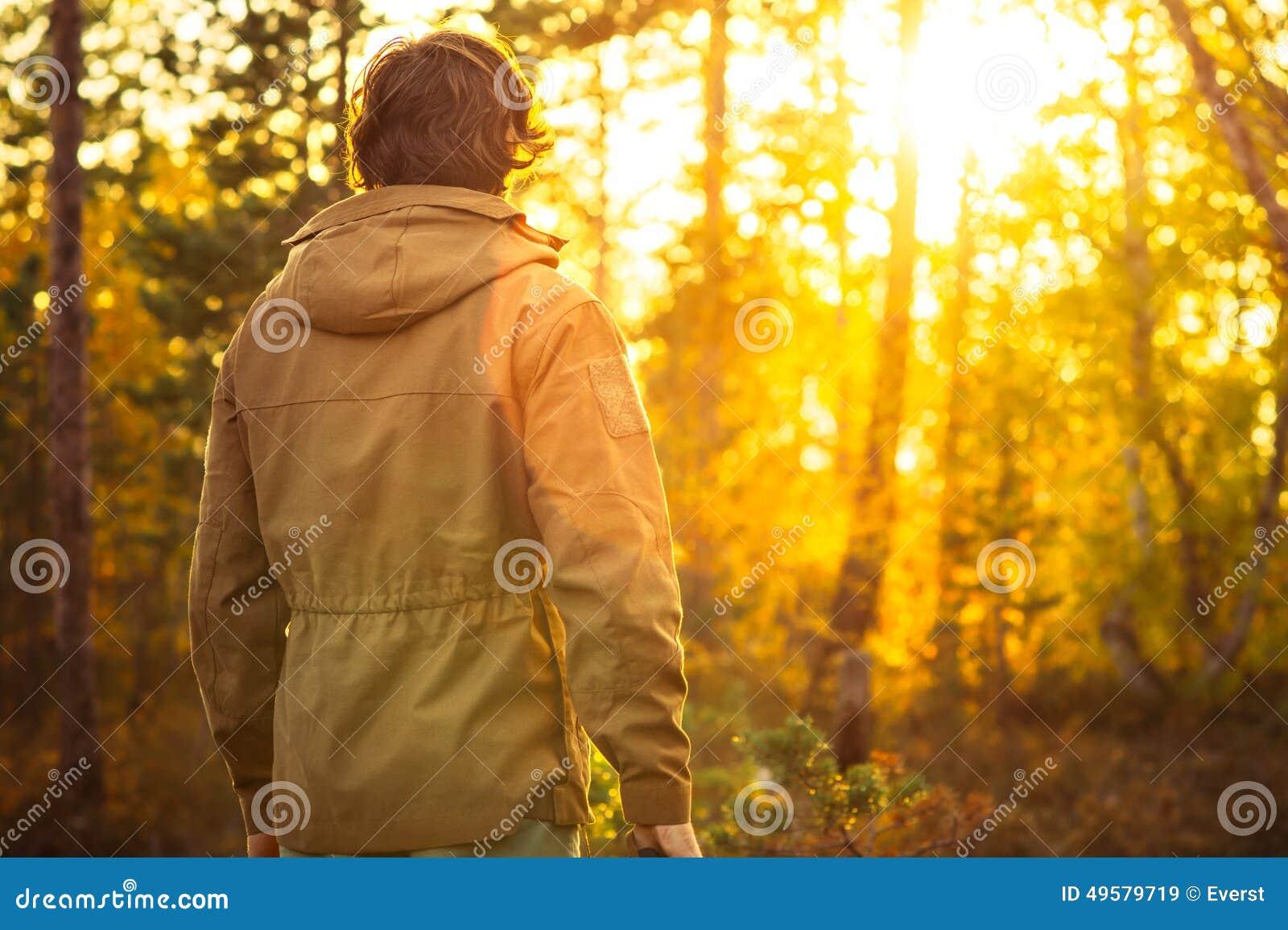 单独站立在森林里的年轻人室外与在背景的日落自然