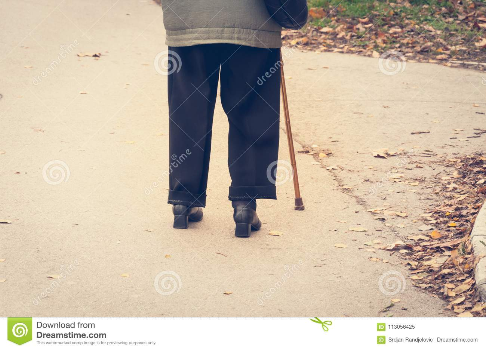 单独老沮丧的妇女步行在街道下有从后面的拐棍或藤茎感觉偏僻和失去的视图