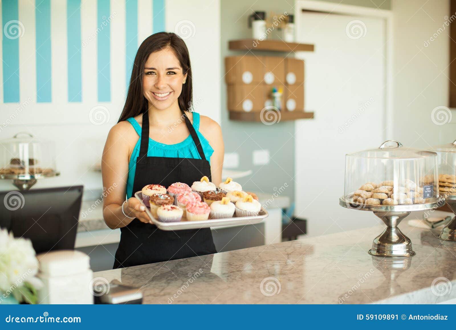卖杯形蛋糕的华美的妇女