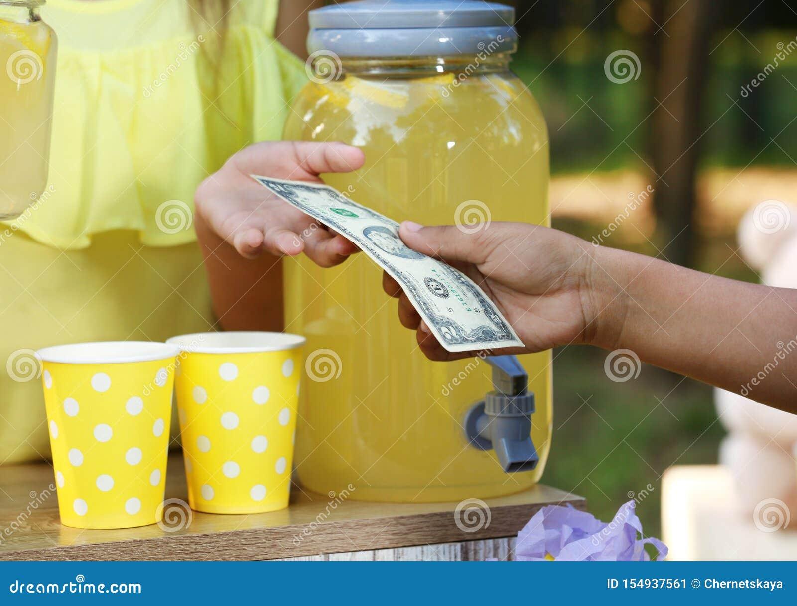 卖自然柠檬水的女孩对非裔美国人的男孩在公园 r