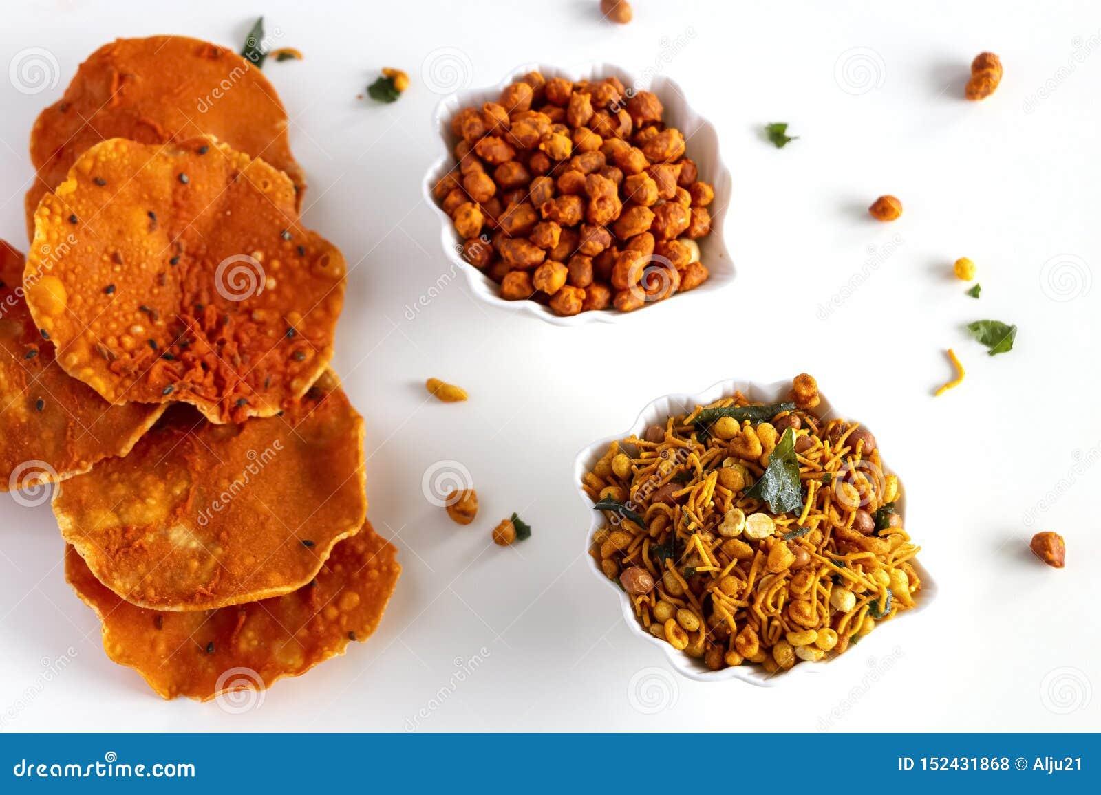 南印度辣嘎吱咬嚼的混合Nimco或Namkeen用花生,米,咖喱叶子和加香料被隔绝的白色碗背景