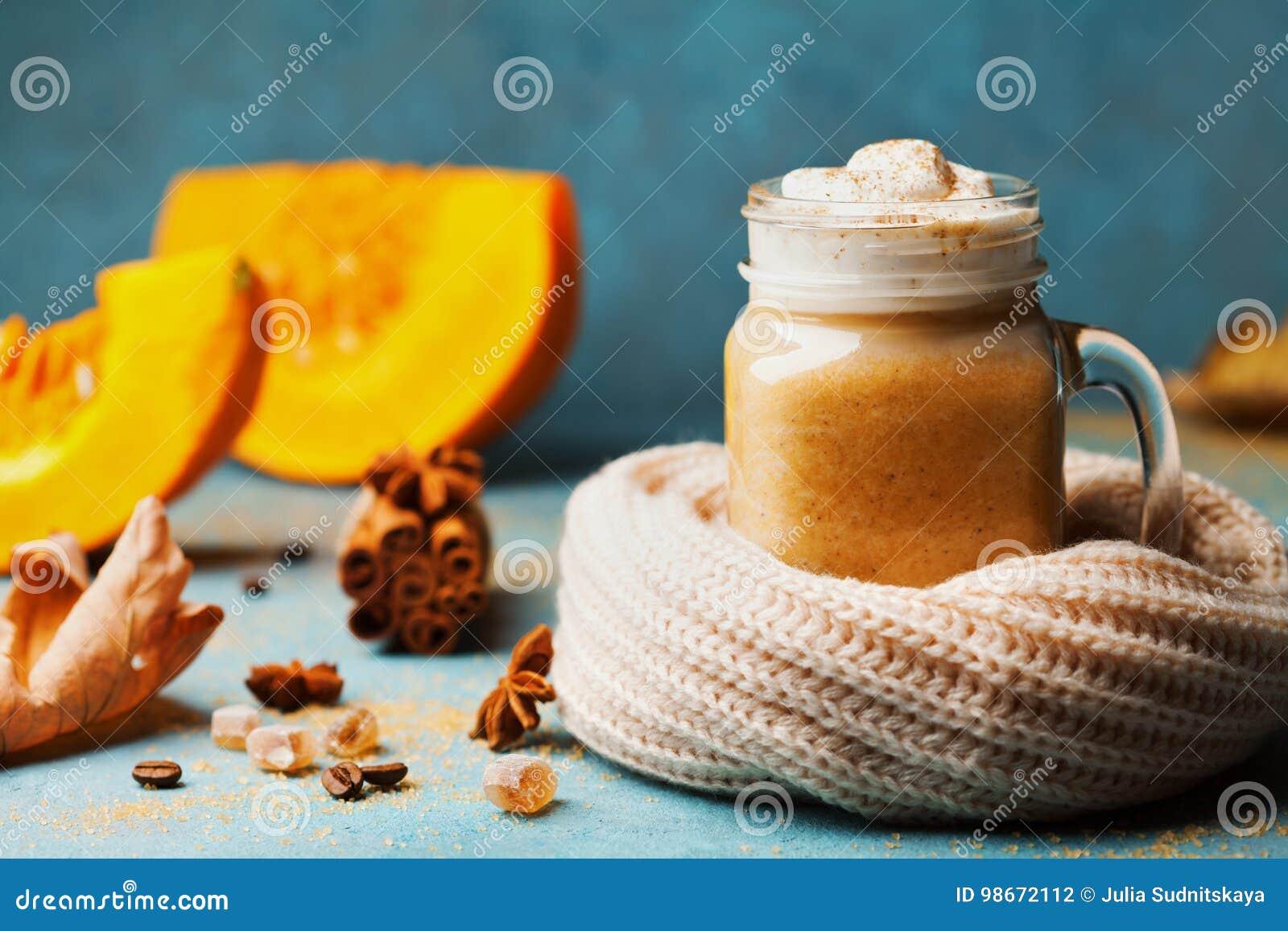 南瓜加了香料拿铁或在装饰的玻璃的咖啡编织了在绿松石葡萄酒背景的围巾 秋天、秋天或者冬天热的饮料