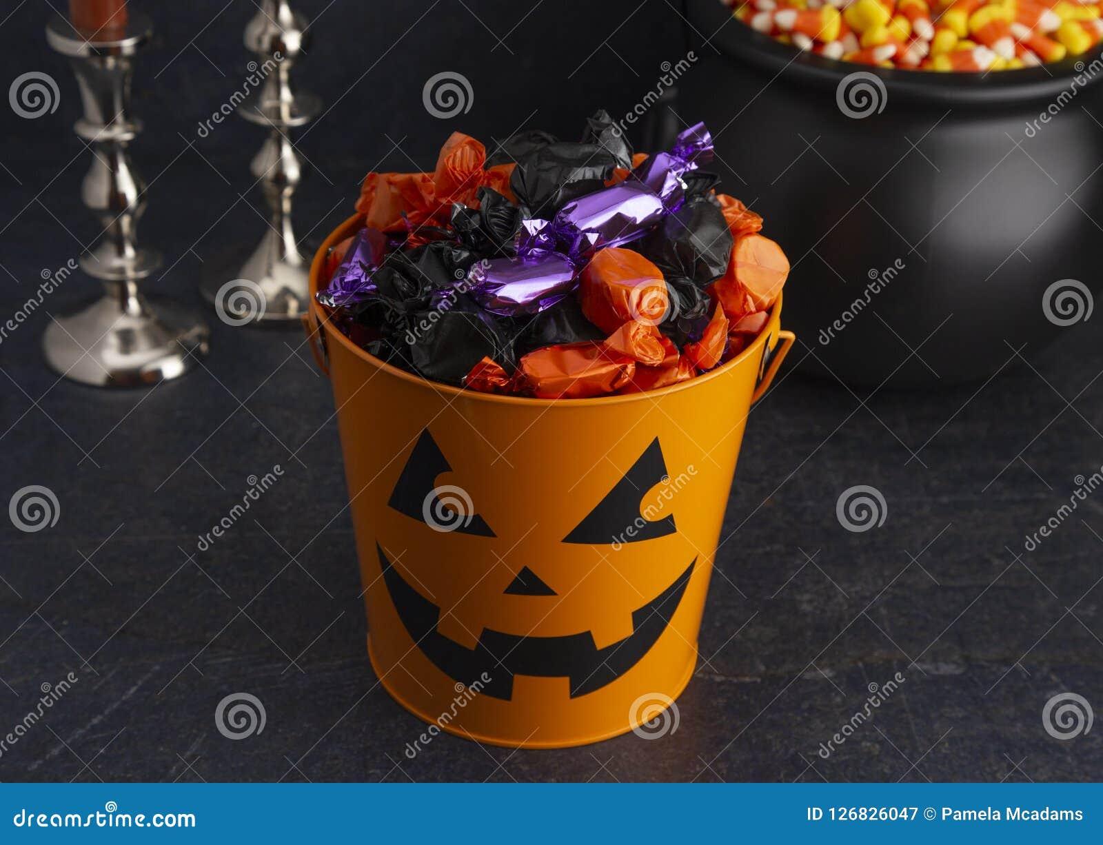 南瓜桶充满各种各样的被包裹的糖果