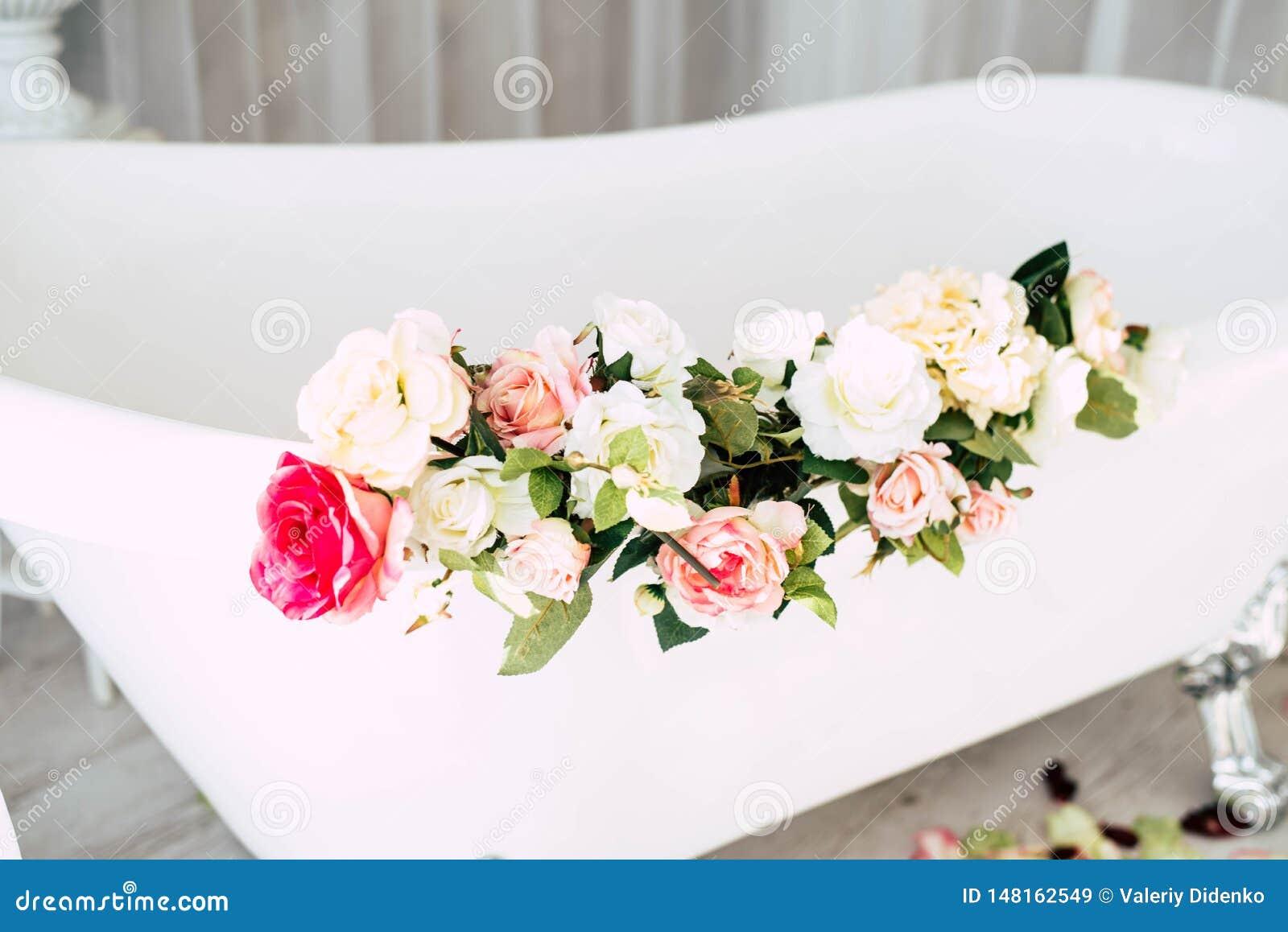 卫生间在用玫瑰的花和瓣装饰的一间轻的屋子