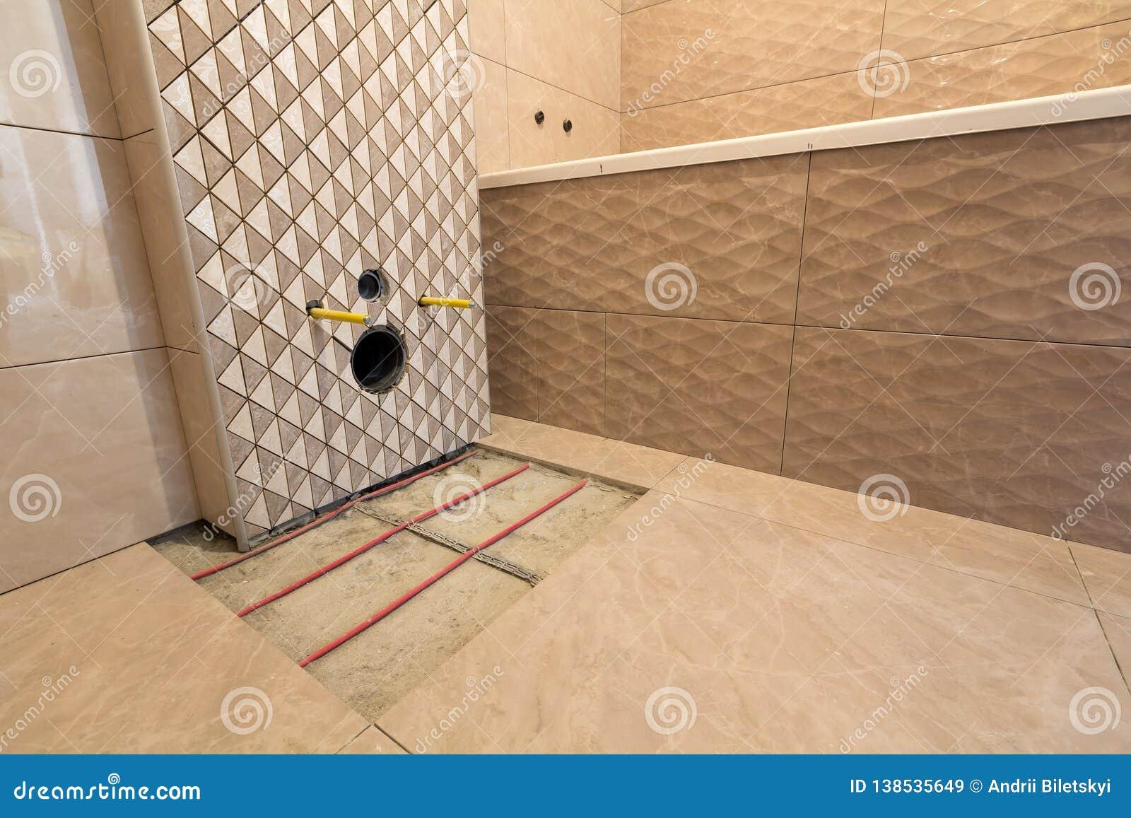 卫生间的未完成的重建有在墙壁,加热电子在水泥地板上的安装的瓷砖的电缆系统和