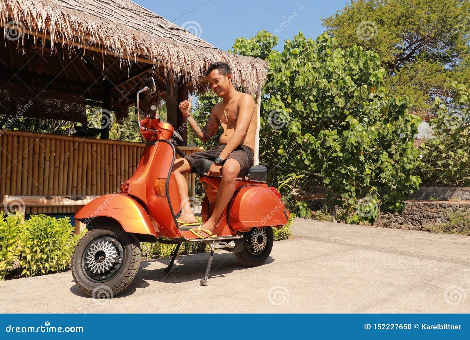 印度尼西亚人坐传统意大利滑行车 橙色古板的摩托车,运输印度尼西亚传统方式