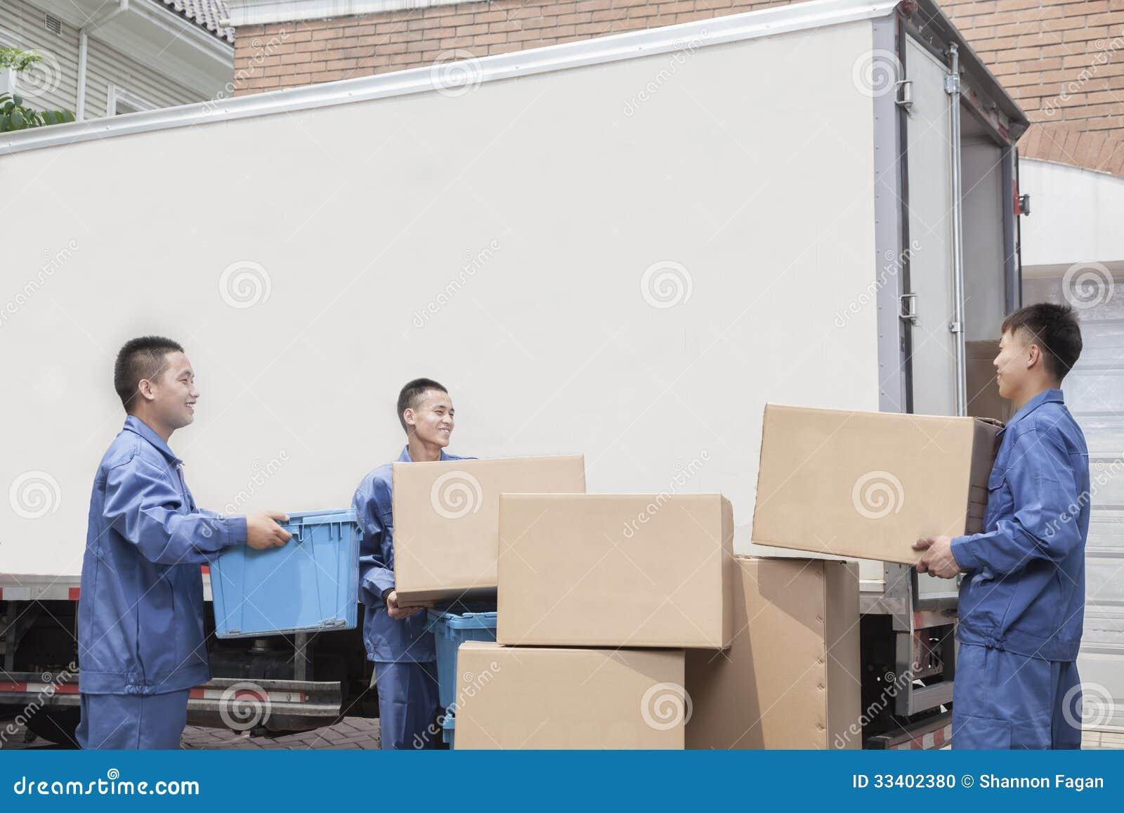 卸载一辆移动货车,许多被堆积的纸板箱的搬家工人