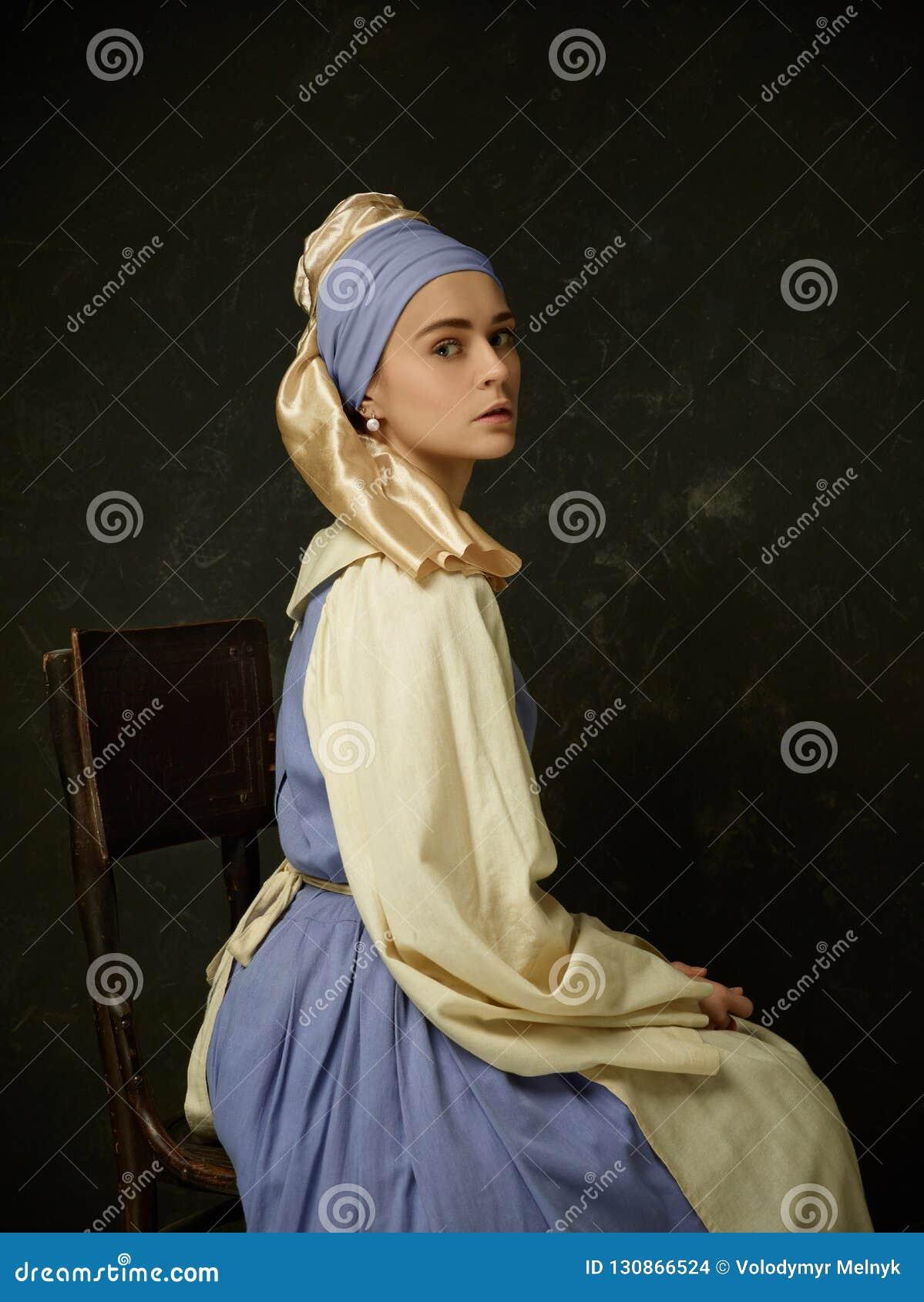 历史服装佩带的束腰礼服和帽子的中世纪妇女