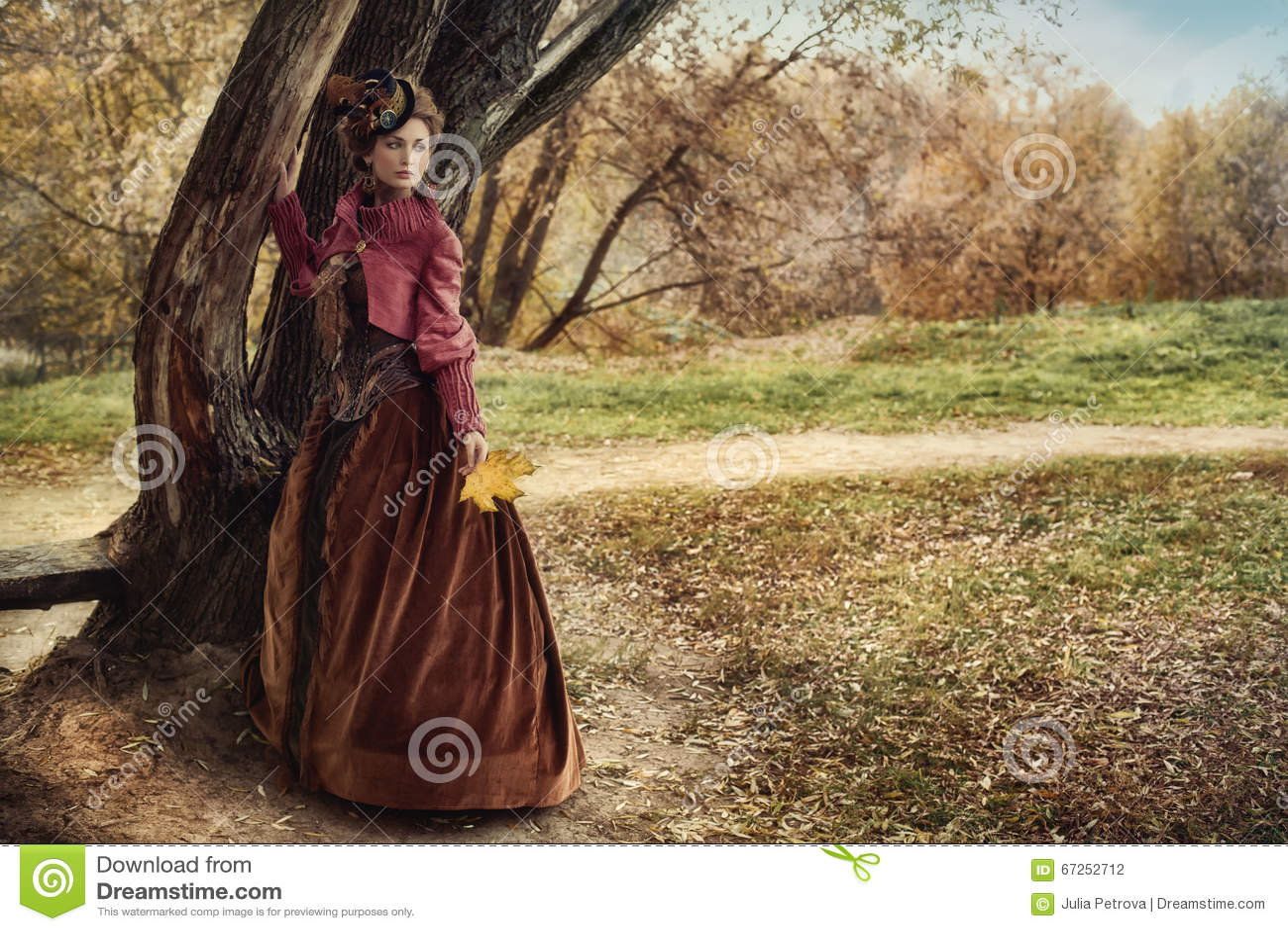 历史礼服的妇女在树附近在秋天森林里