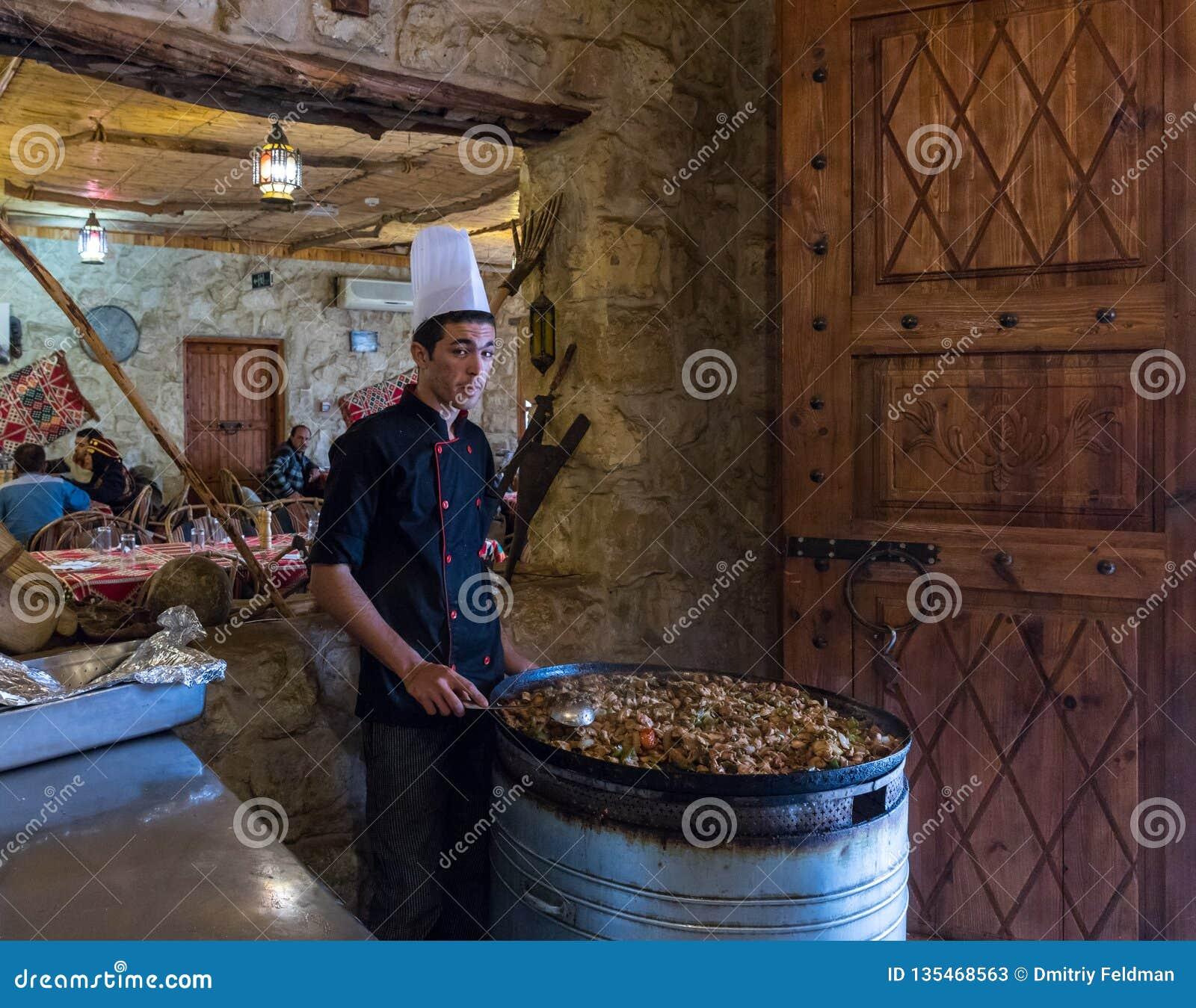 厨师在有肉盘的一个大盘子附近站立并且在Jor的旱谷附近等待访客在路边餐厅芭蕉科城市