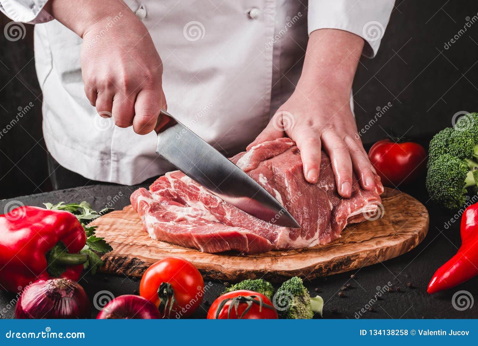 厨师屠户切口与刀子的猪肉在厨房,烹调食物