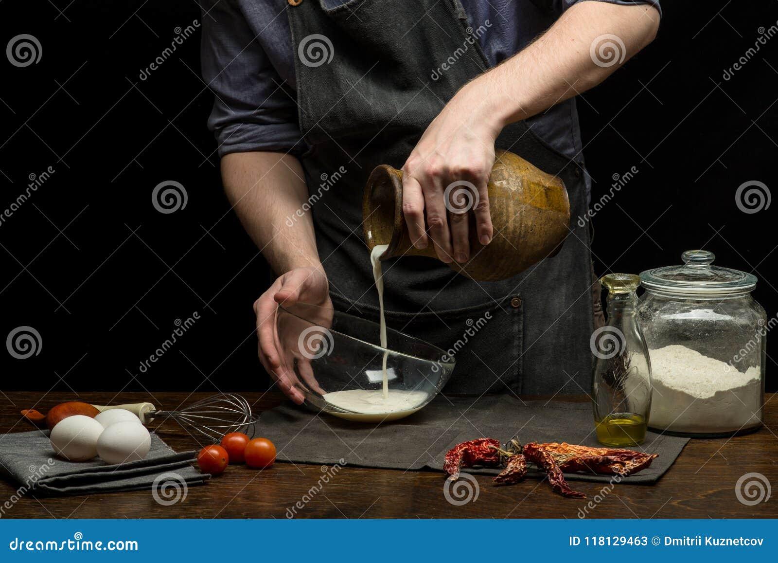 厨师手倒从赤土陶器瓶子的牛奶准备面团