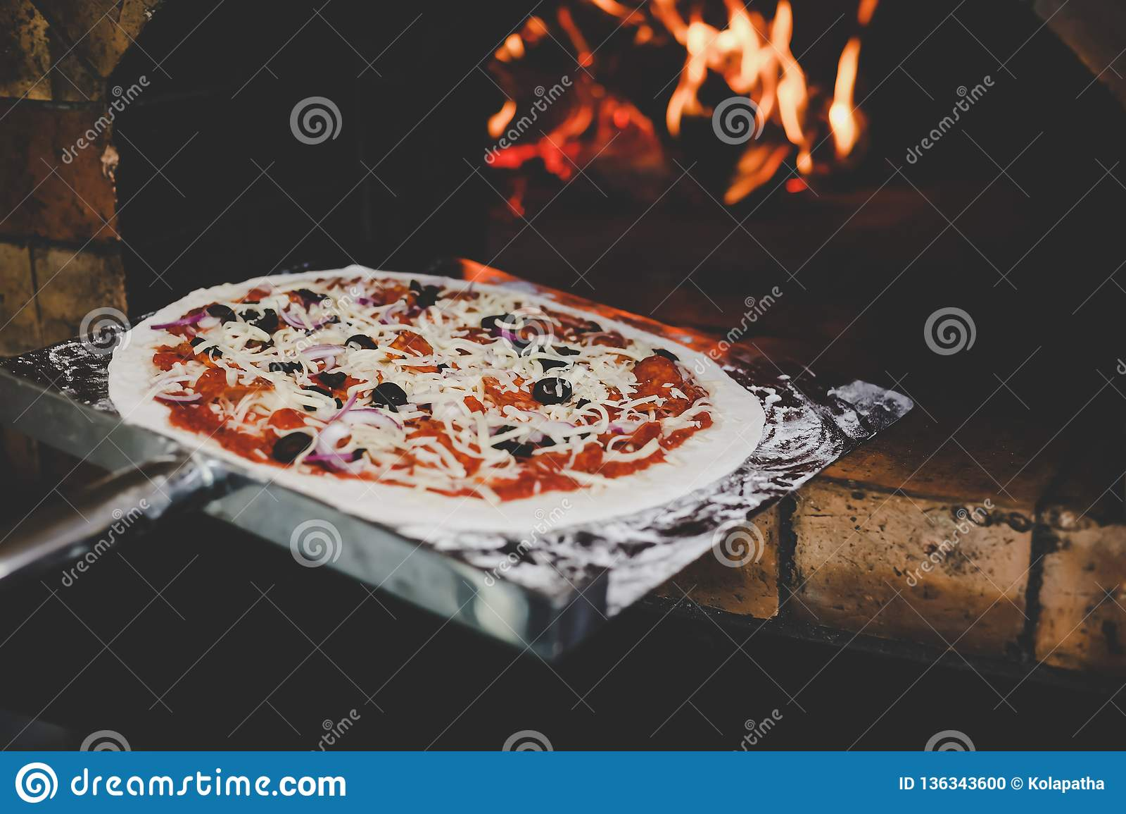 厨师用途不锈的小铲,投入了可口未加工的比萨对被烘烤的比萨的火炉 It's著名意大利料理 他烹调比萨为