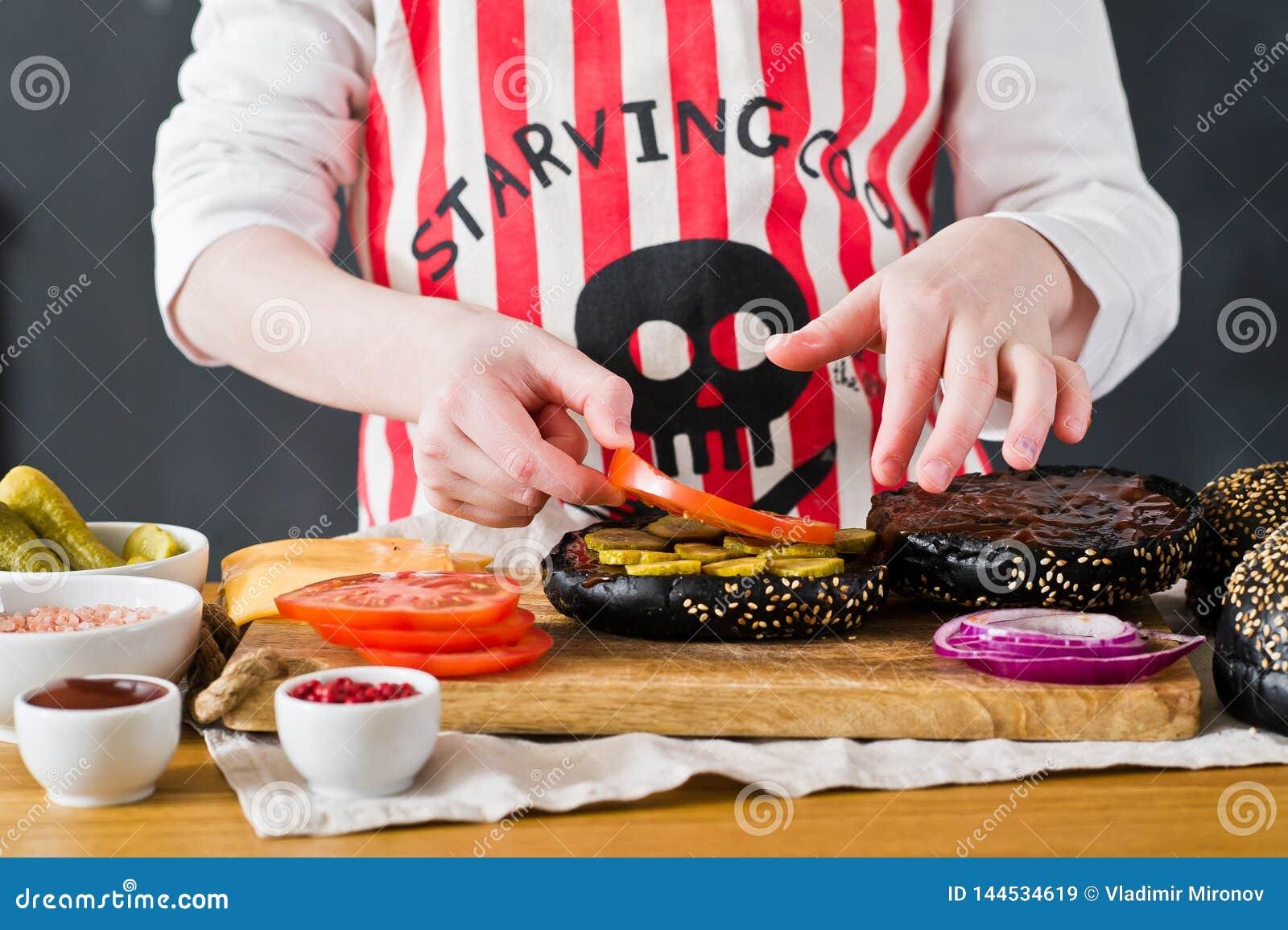 厨师的围裙的一个孩子在厨房里准备一个汉堡 烹调黑cheeseberger的食谱 自创水多的汉堡