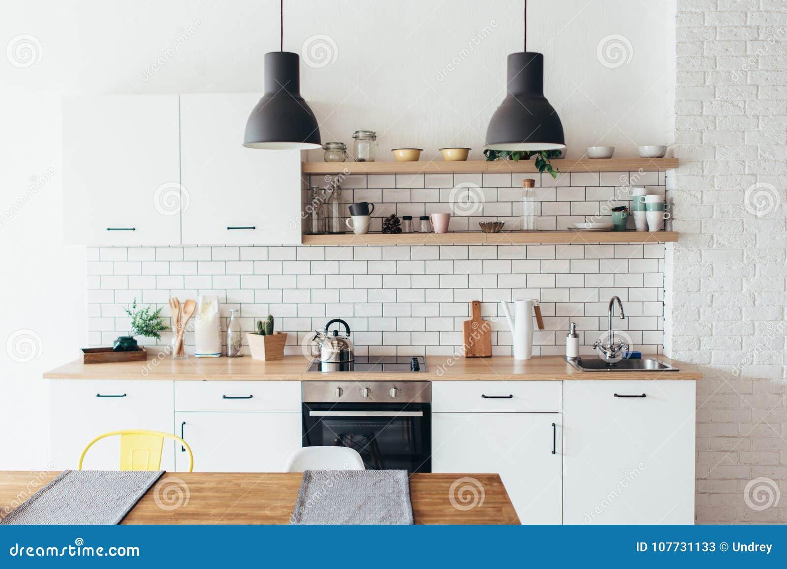 厨房现代新的轻的内部有白色家具和餐桌的