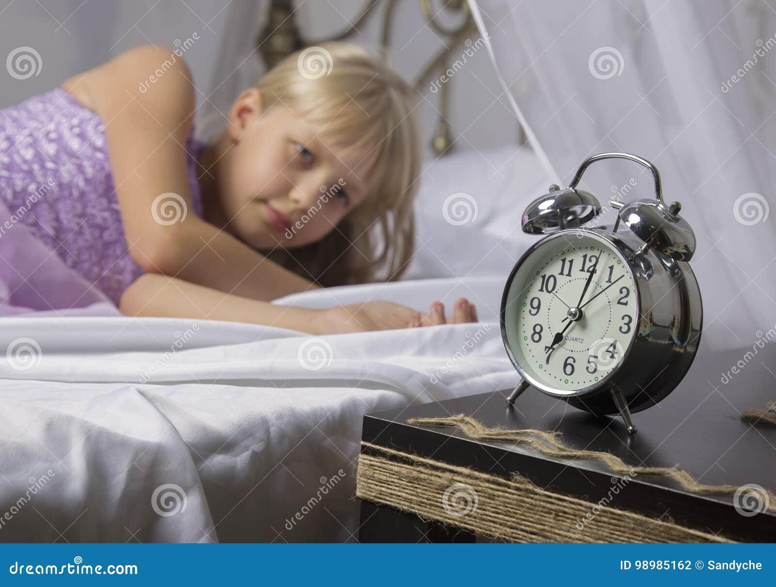 及早唤醒 停止在一张床上的醒一个睡着的女孩闹钟早晨