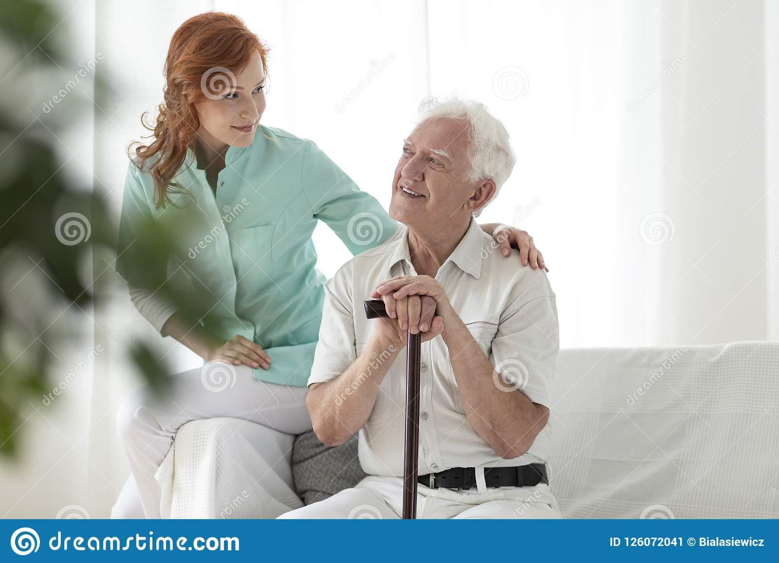 友好的护士和微笑的年长人用拐棍在