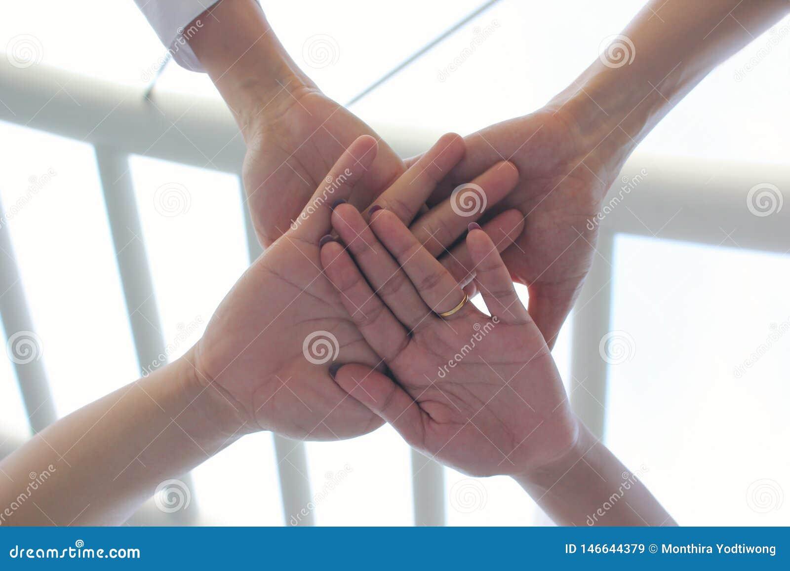 友谊,遇见配合概念,有显示在自然绿色背景的堆的小组人手团结
