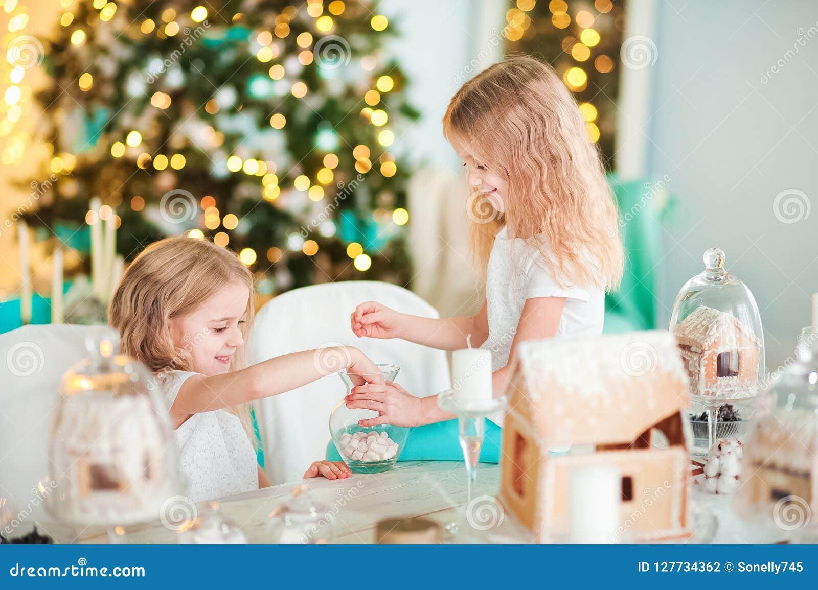 双姐妹在一张桌上在使用与一个姜房子的厨房里新年 明亮的颜色的厨房装饰