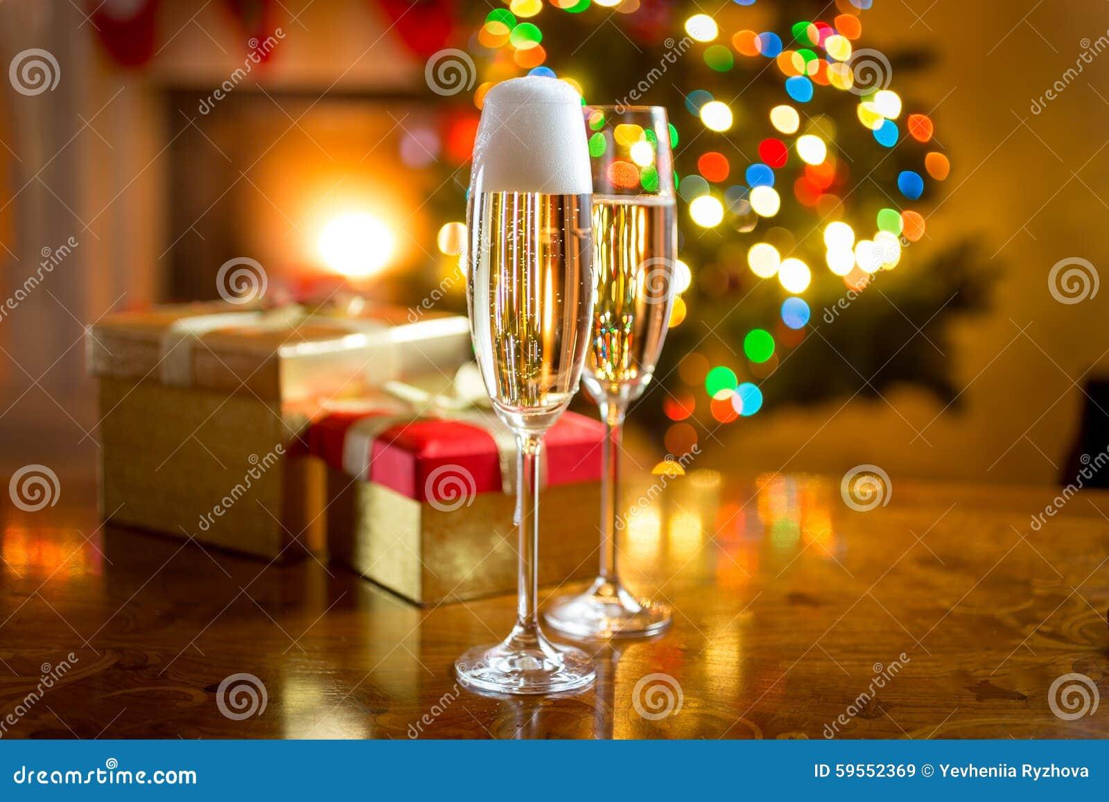 反对为圣诞节装饰的壁炉的两块香槟玻璃