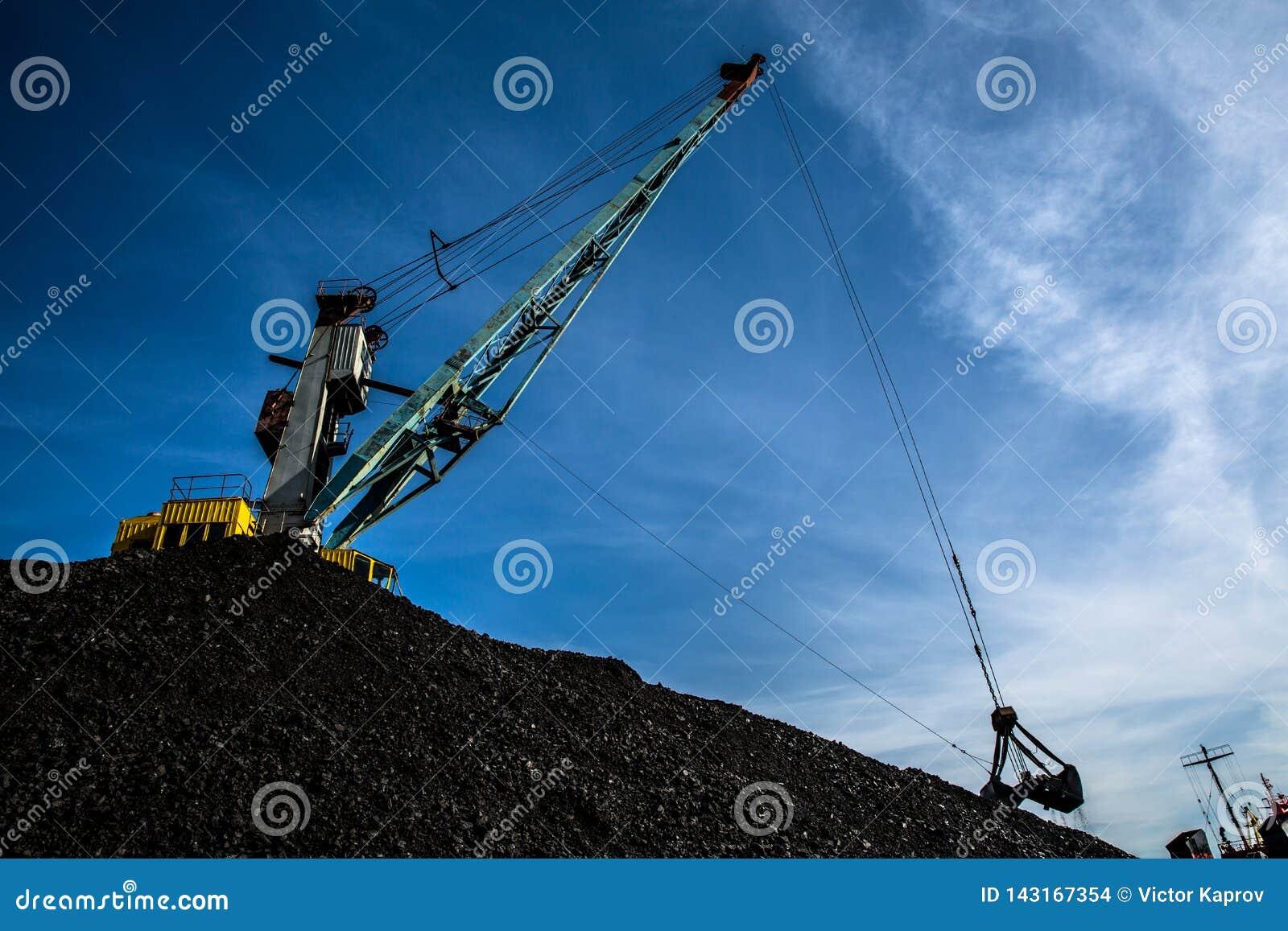 反对天空蔚蓝和云彩的港口起重机装载的煤炭