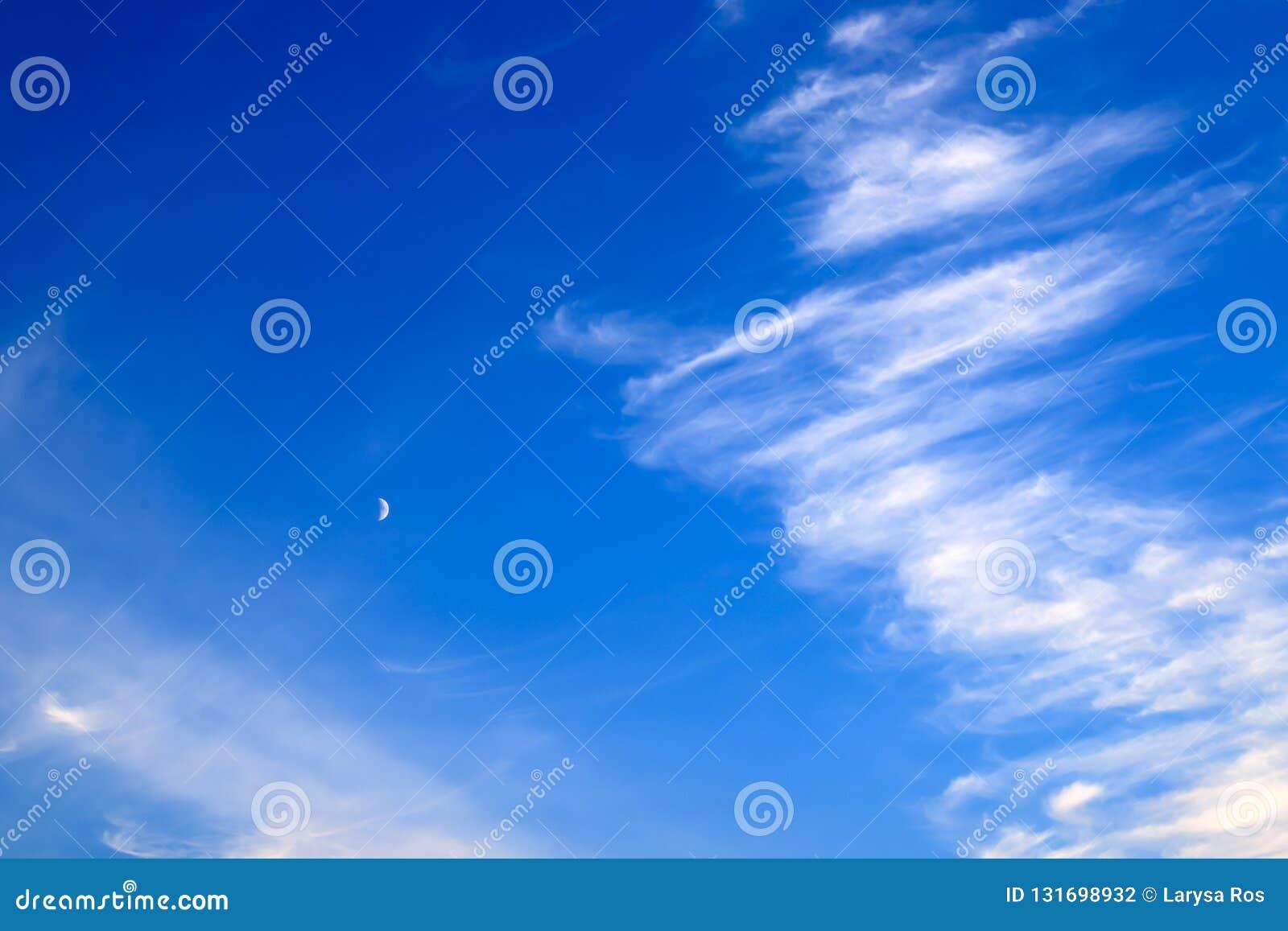 反对天空蔚蓝的美丽的美丽如画的胆怯云彩与年轻月亮,不可思议的浪漫背景