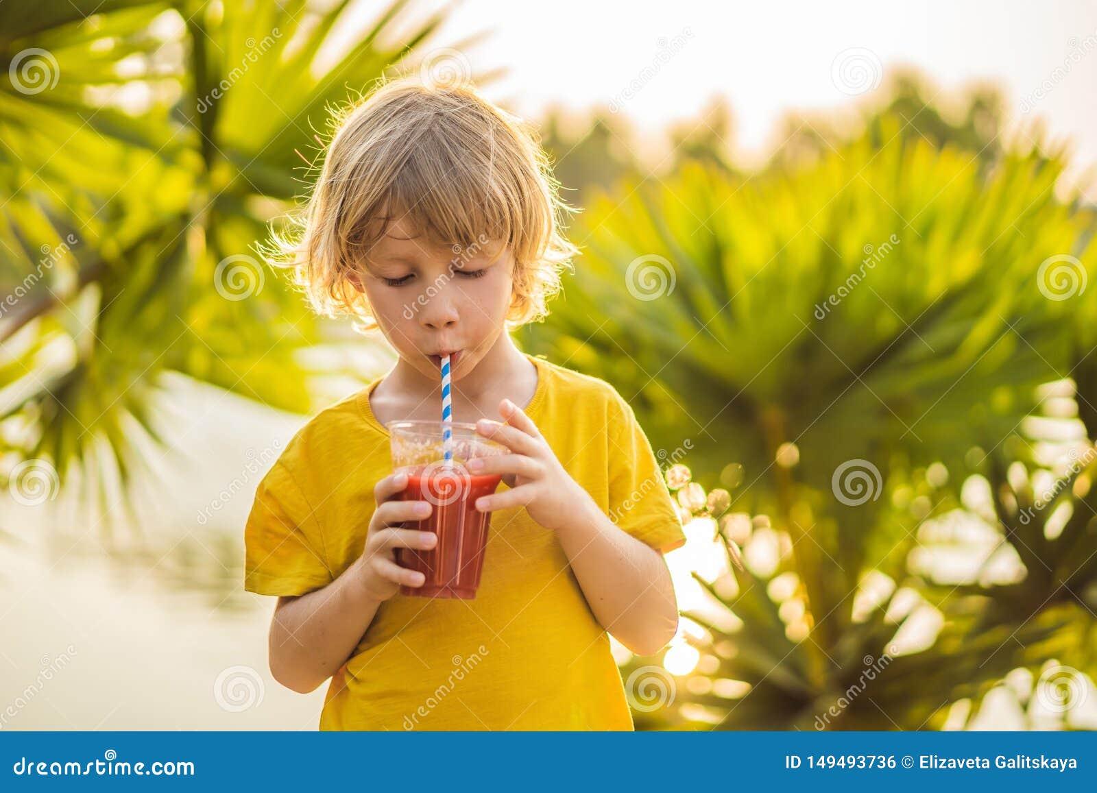 反对棕榈树背景的男孩饮料健康圆滑的人  西瓜圆滑的人 健康营养和维生素为