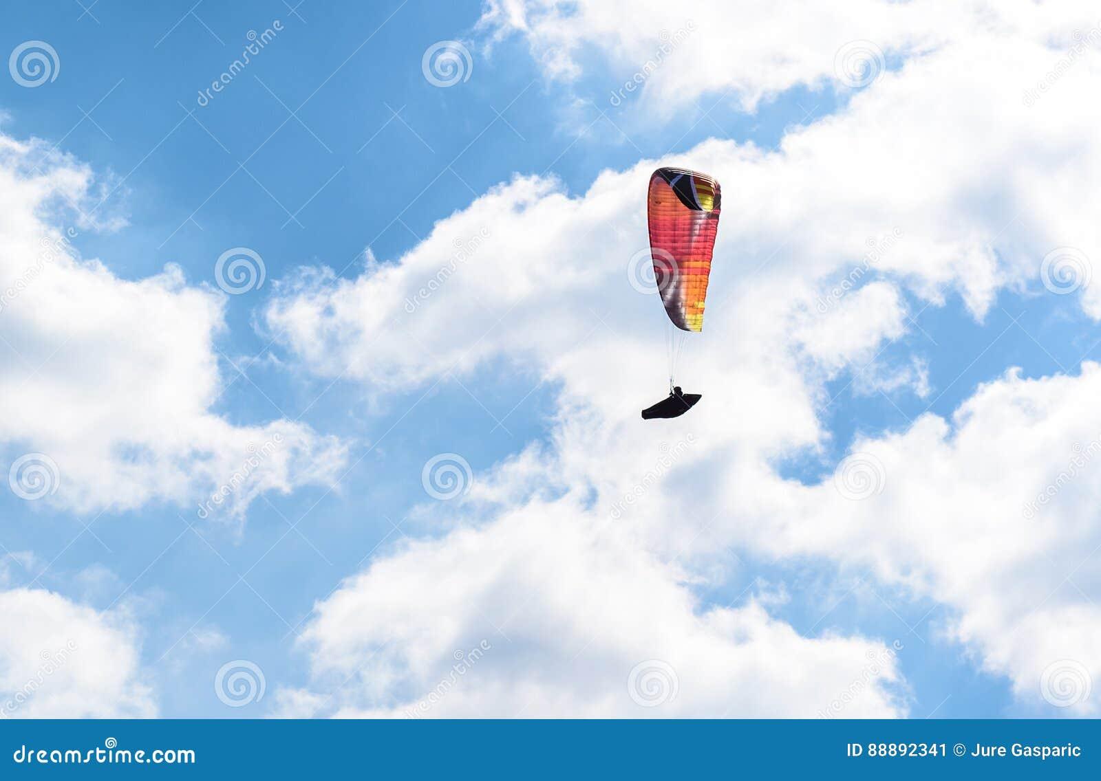反对蓝天的滑翔伞飞行与白色云彩