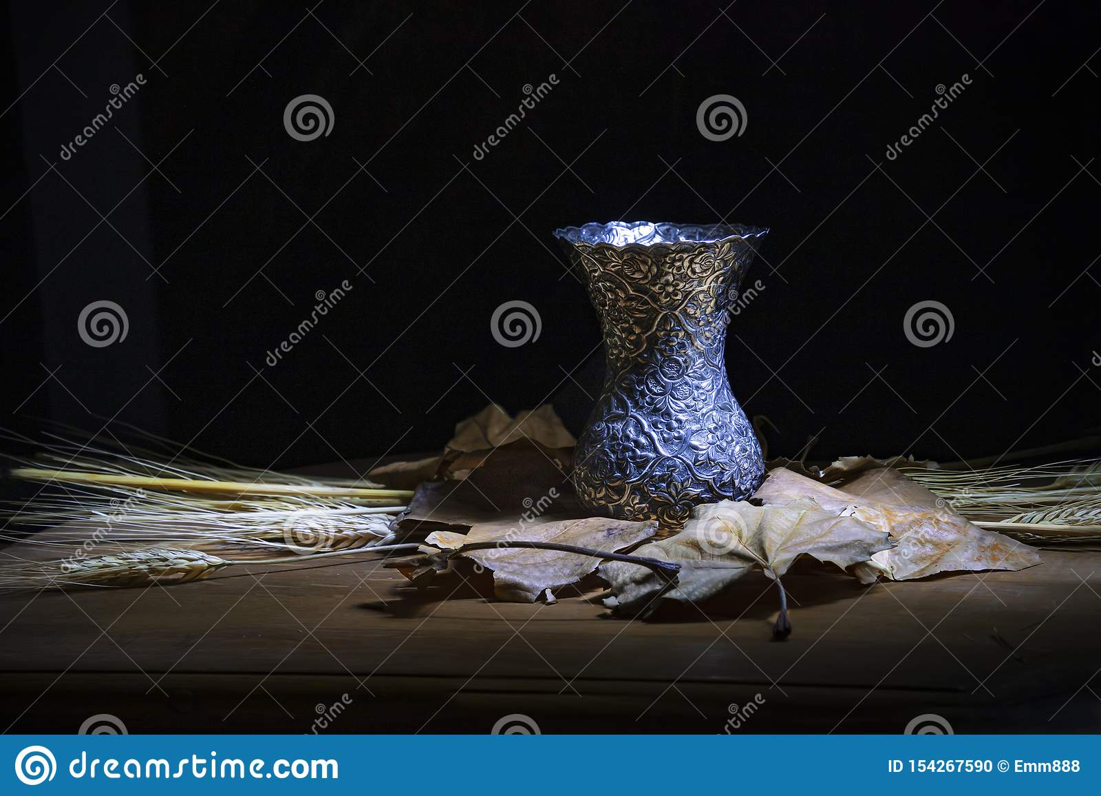 反对黑暗的背景的静物画 金属在麦子干燥叶子和茎的花瓶身分