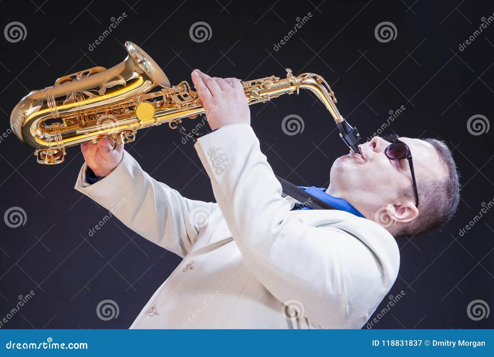 反对黑背景的萨克斯管吹奏者 水平的图象取向