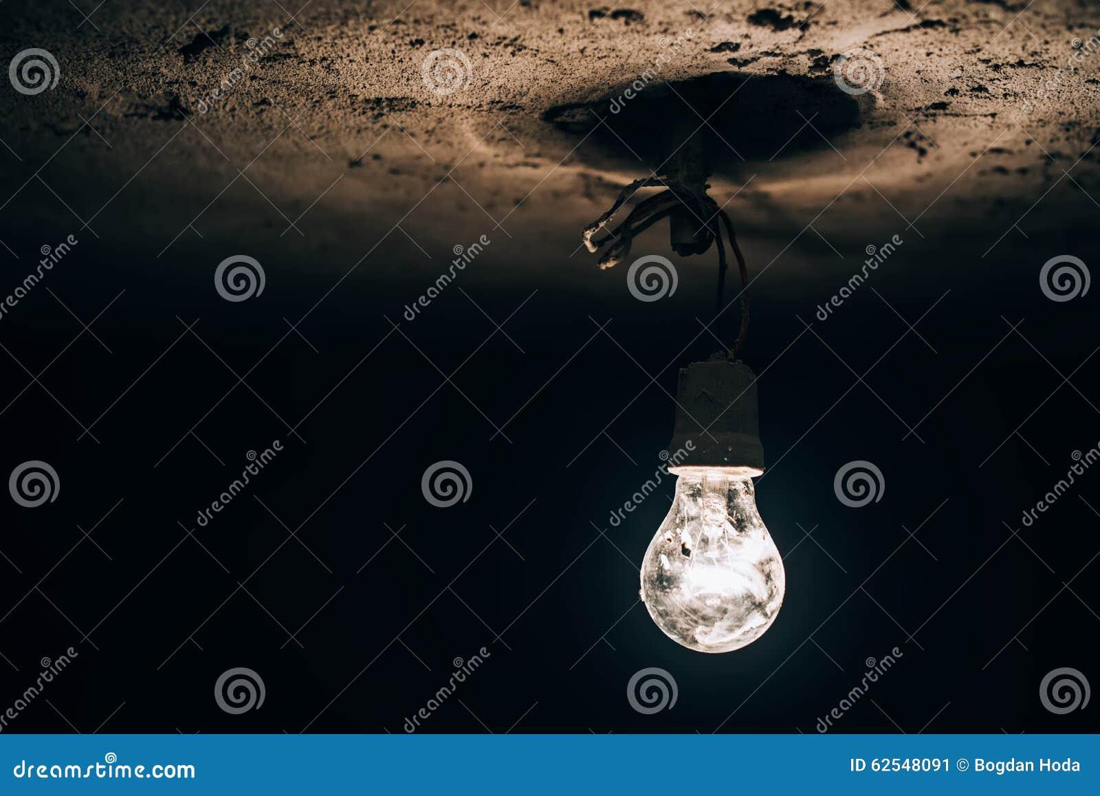 发光在黑暗的地下室的老电灯泡 在建造场所的电即兴创作