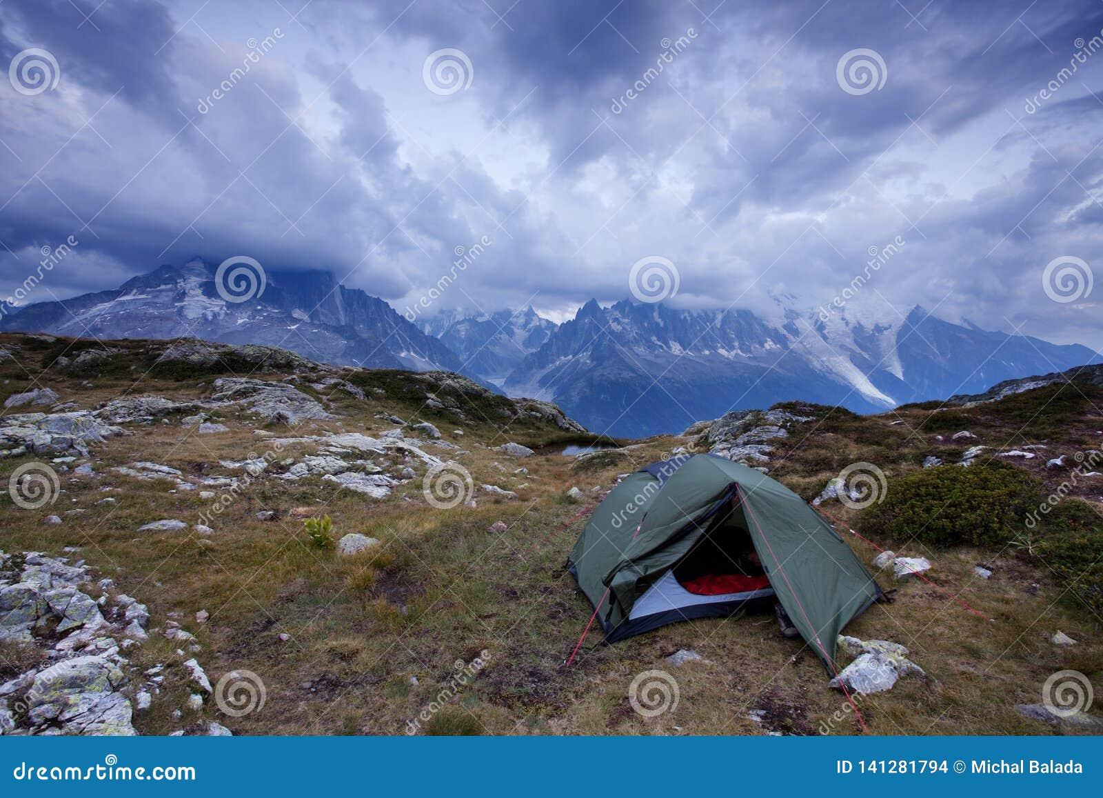 发光由阳光的高山谷 绿色帐篷在牧场地 受欢迎的旅游胜地 与帐篷的剧烈和美丽如画的场面