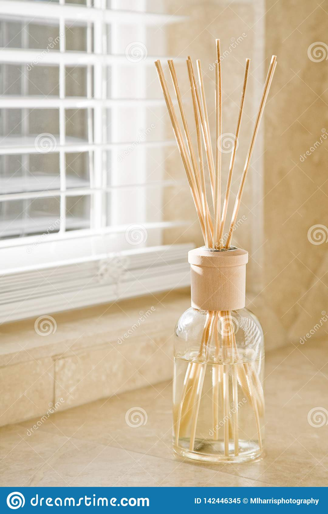 发光通过在芬芳分散器上的窗帘的阳光在石瓦片卫生间柜台 干净,明亮,新房子家