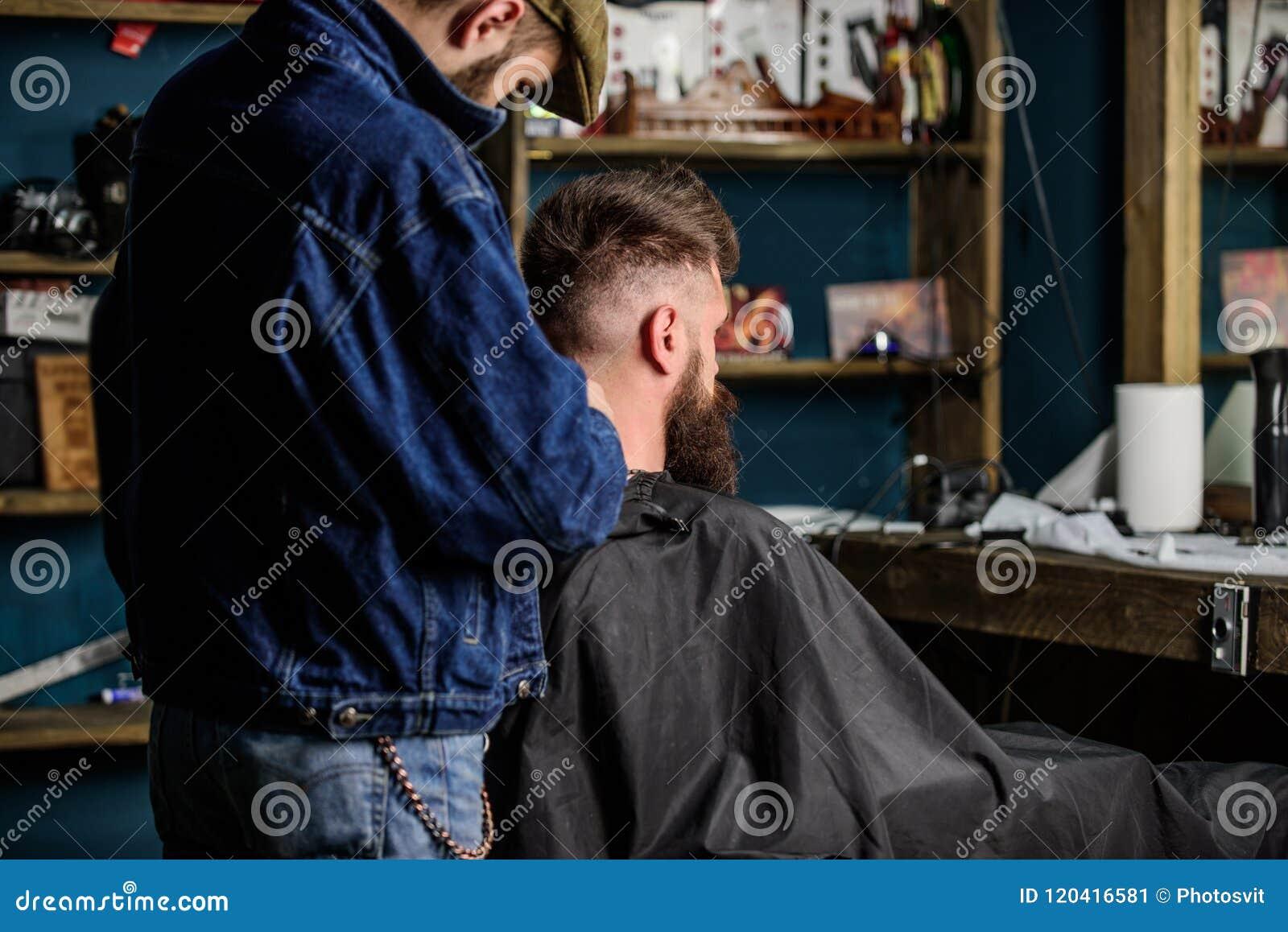 发型服务概念 有飞剪机的理发师在有胡子的人的,理发店背景发型工作 行家