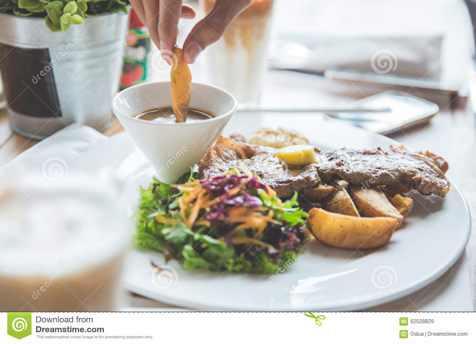 发牢骚格栅牛排用沙拉和油煎的土豆楔子