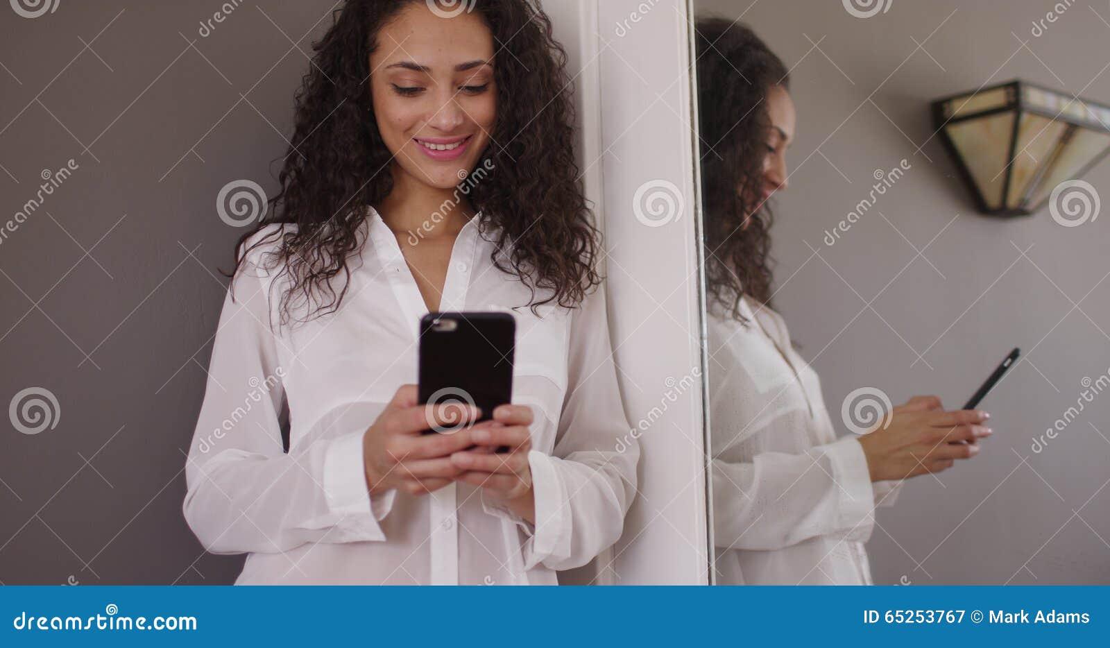 发短信在镜子前面的迷人的年轻女性深色的模型