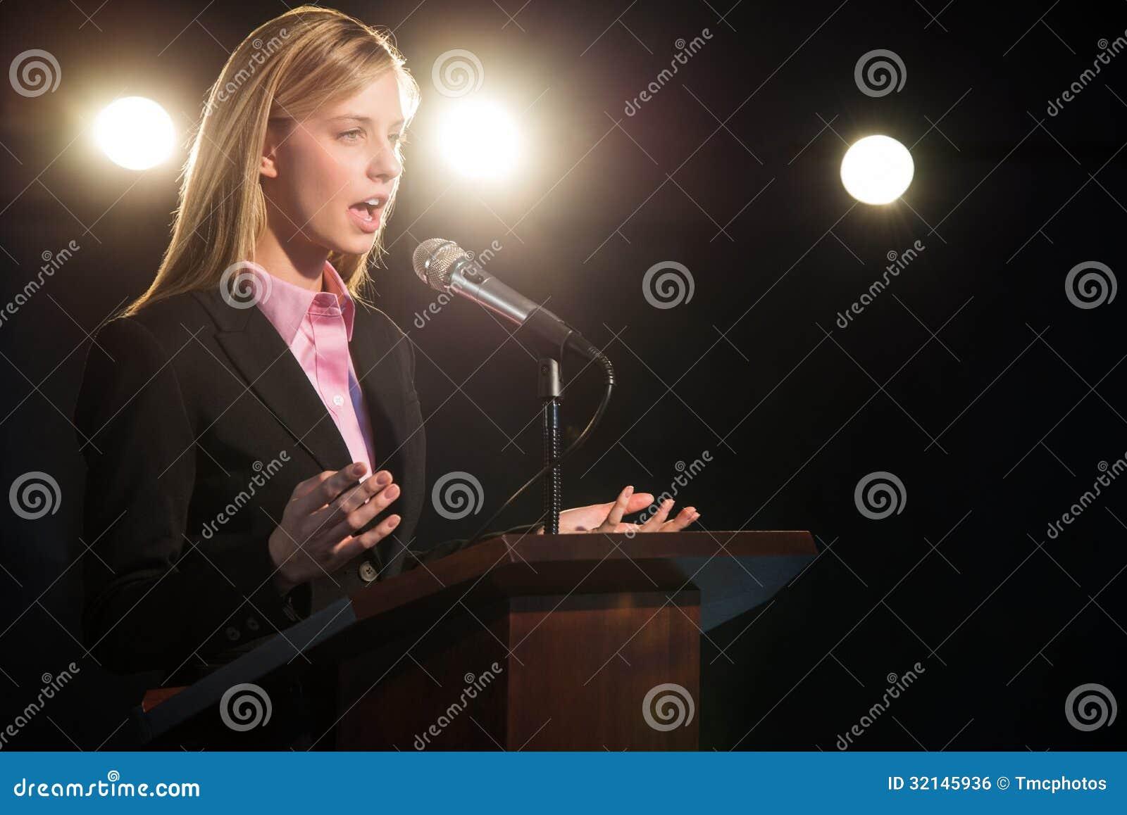 发表讲话的女实业家在指挥台在观众席
