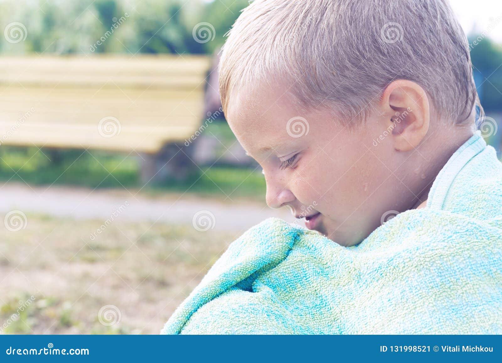 取暖在游泳以后的小白种人男孩在湖 男孩用毛巾盖了自己并且坐岸
