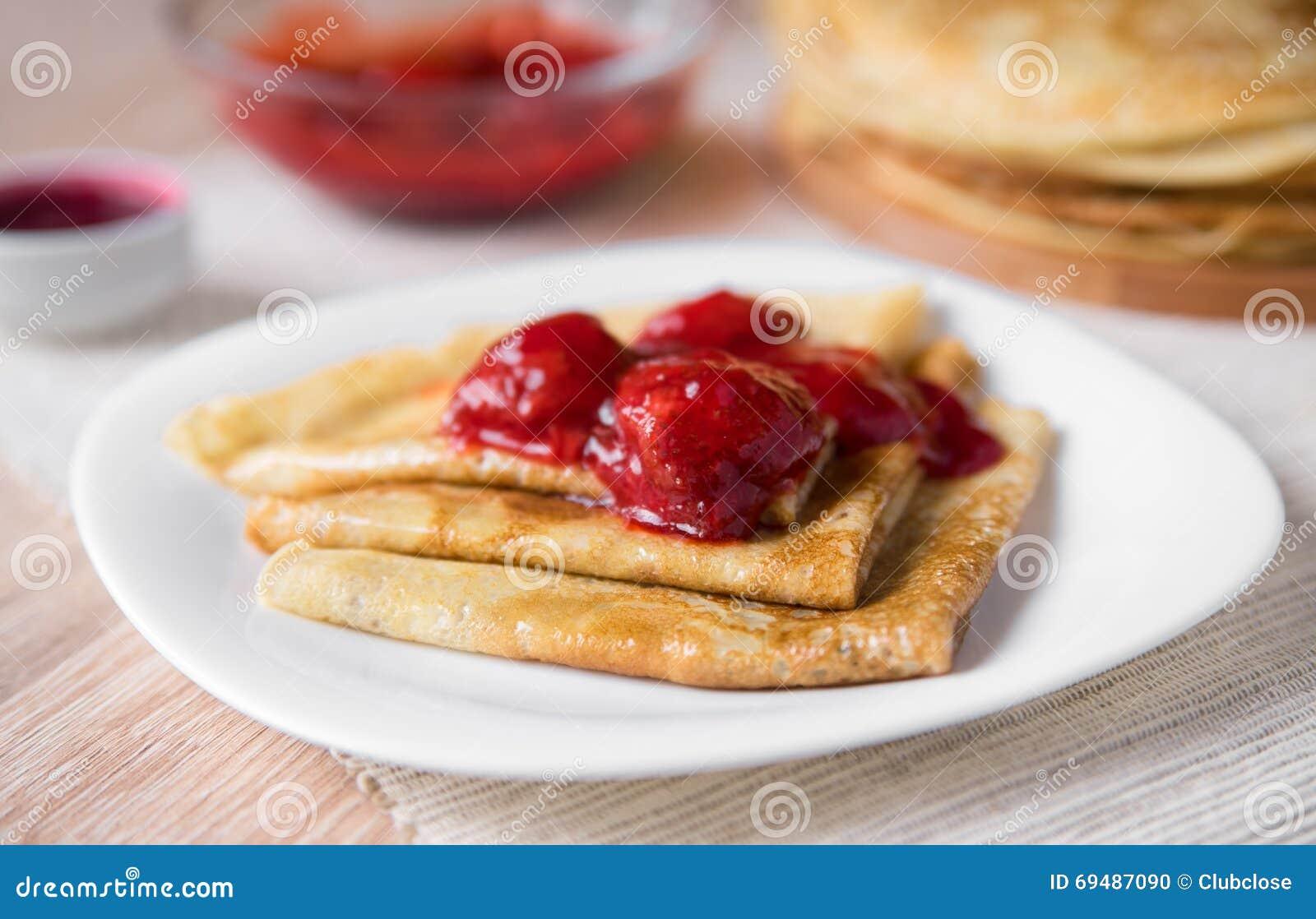 变薄俄国薄煎饼被折叠的三角用在一块白色板材的草莓调味汁