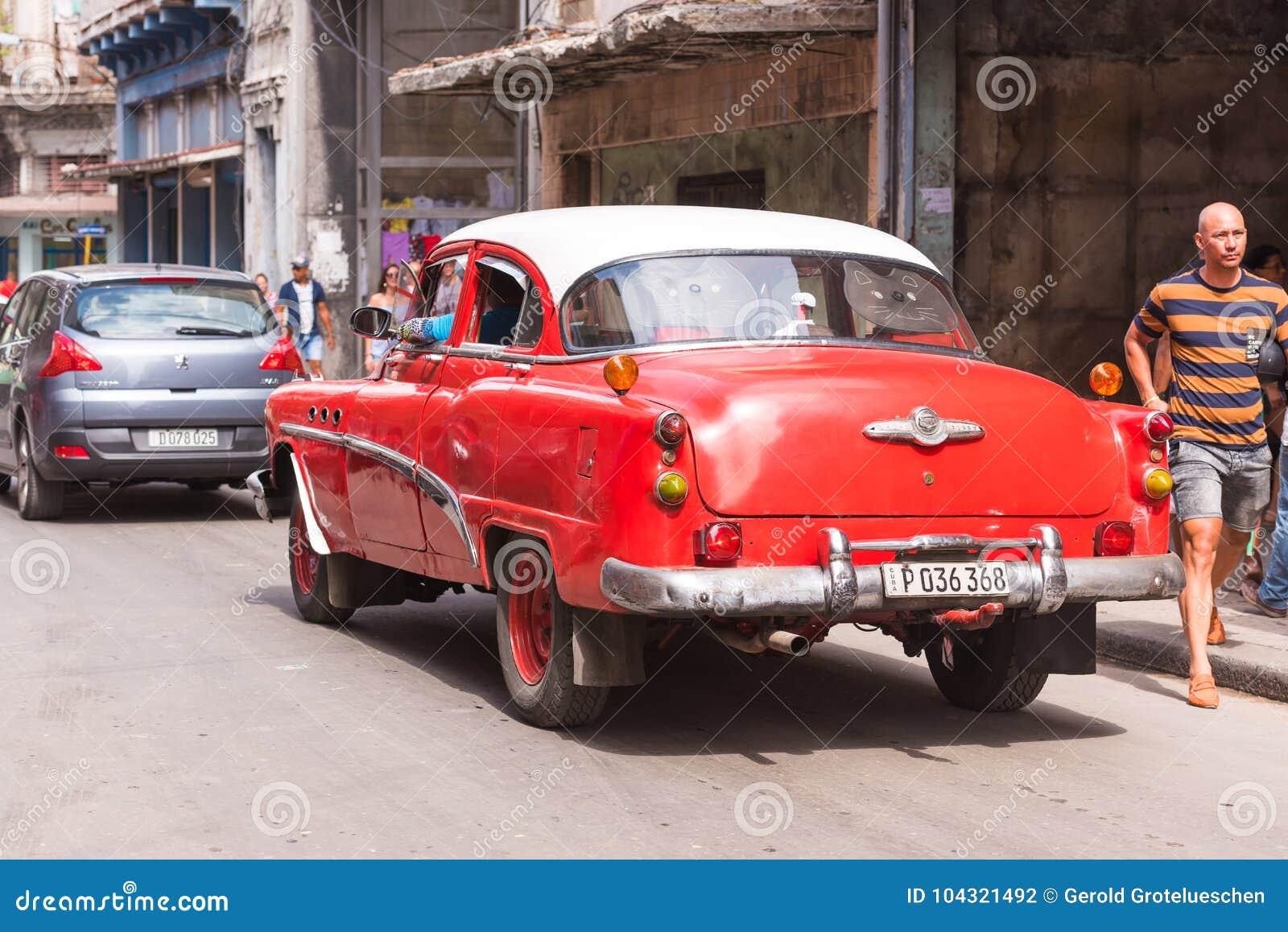 古巴,哈瓦那- 2017年5月5日:在城市街道上的红色美国减速火箭的汽车 复制文本的空间 回到视图