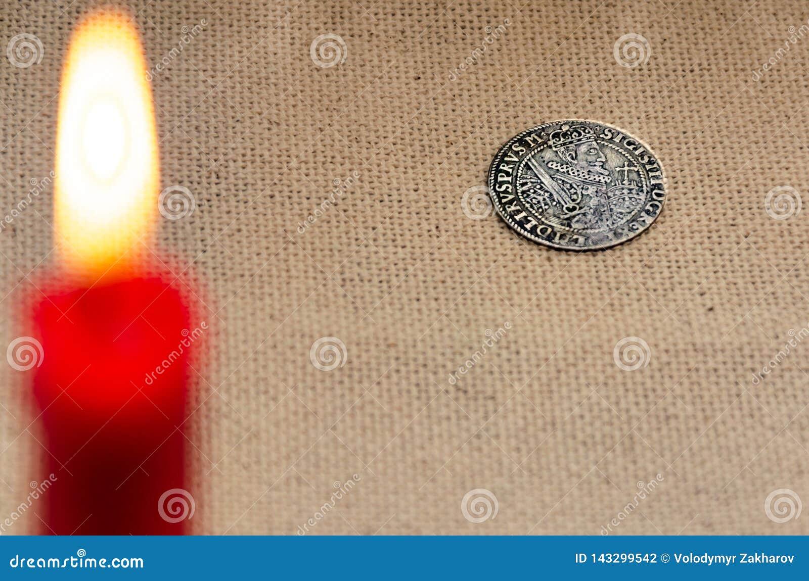 古老银币和燃烧的蜡烛