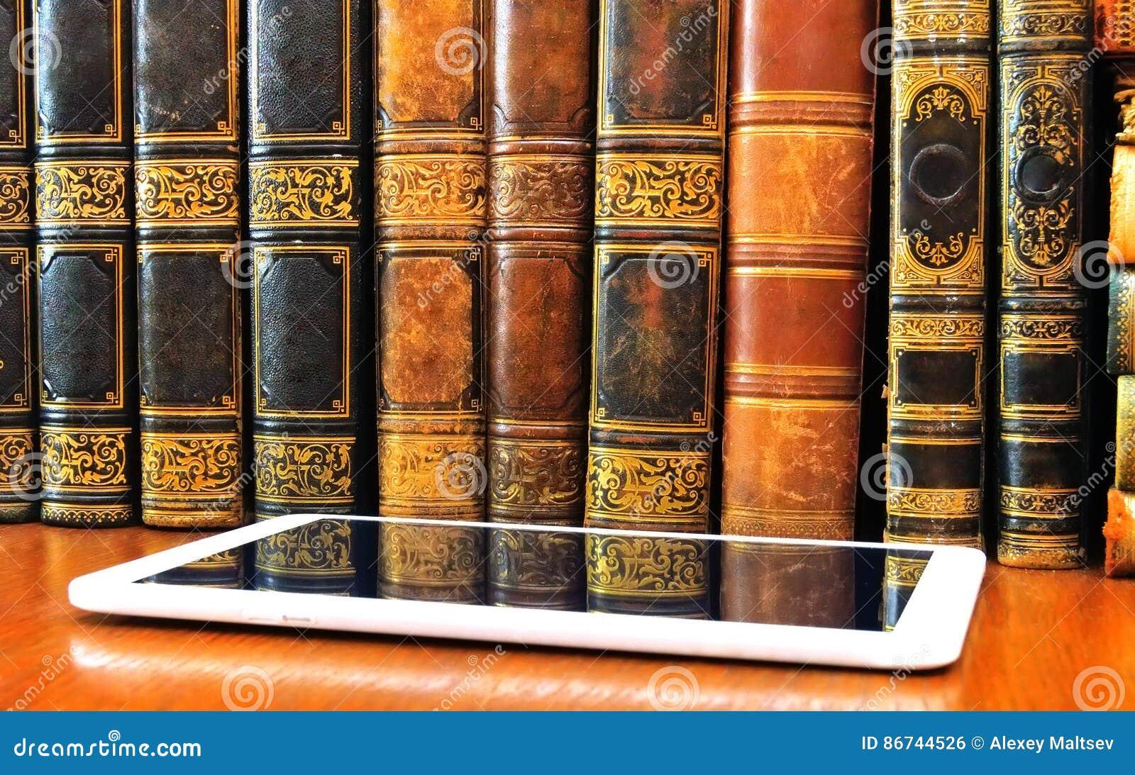 古色古香的书和片剂在桌上