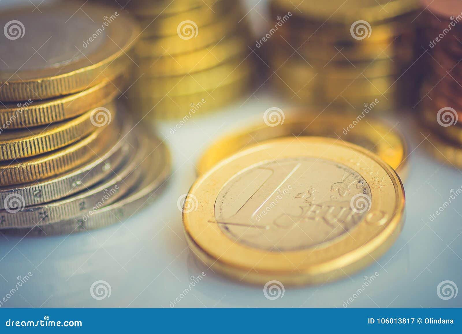 另外价值被堆积的新的发光的白色和金黄欧洲硬币在被定调子的桌面财务投资股票储款概念的