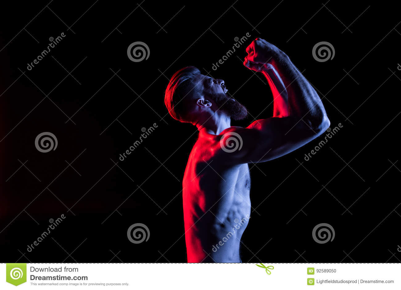 叫喊的爱好健美者打手势和隔绝在与剧烈的照明设备的黑色