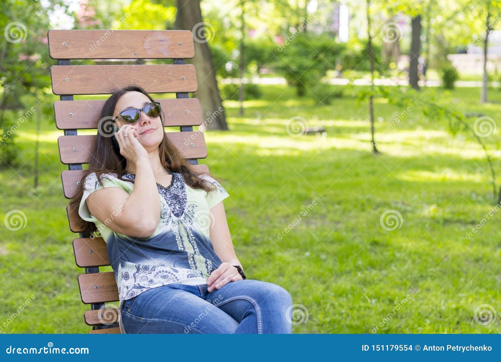 叫时髦时兴的美女谈话在她的手机在公园 美丽的年轻女人谈话手机一会儿